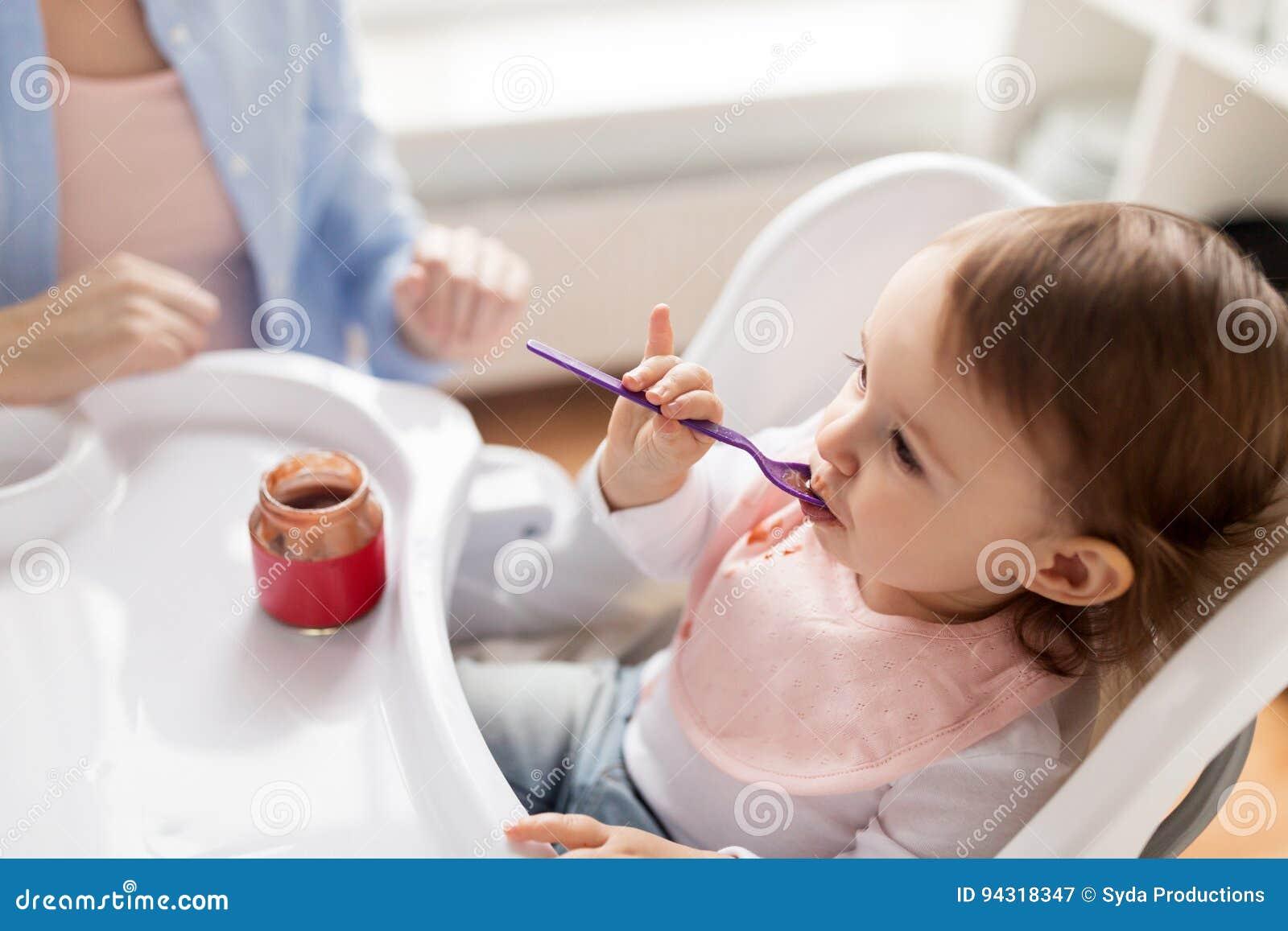 Bébé avec la cuillère mangeant de la purée du pot à la maison
