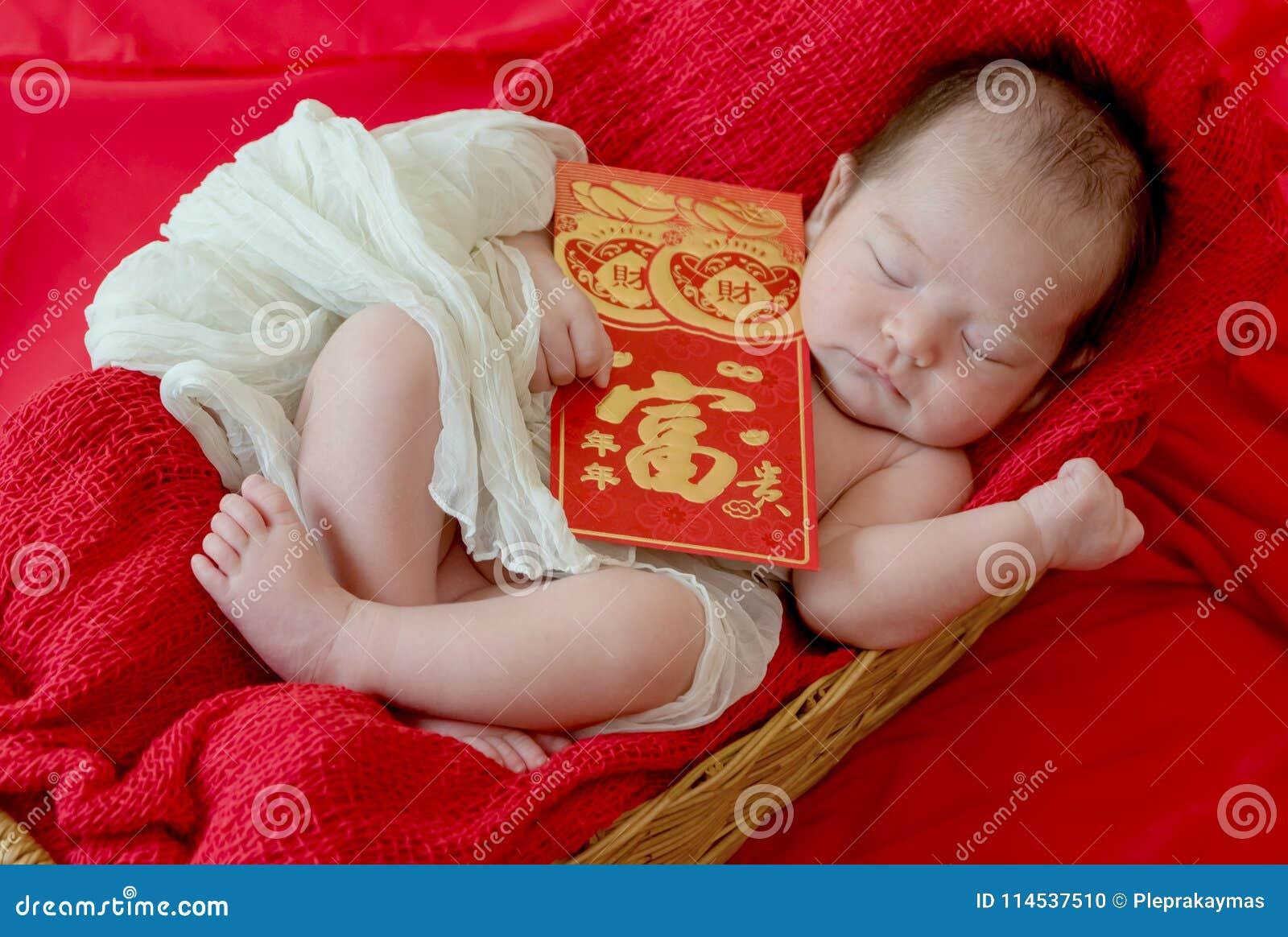 Bébé avec le geste de la nouvelle année chinoise heureuse