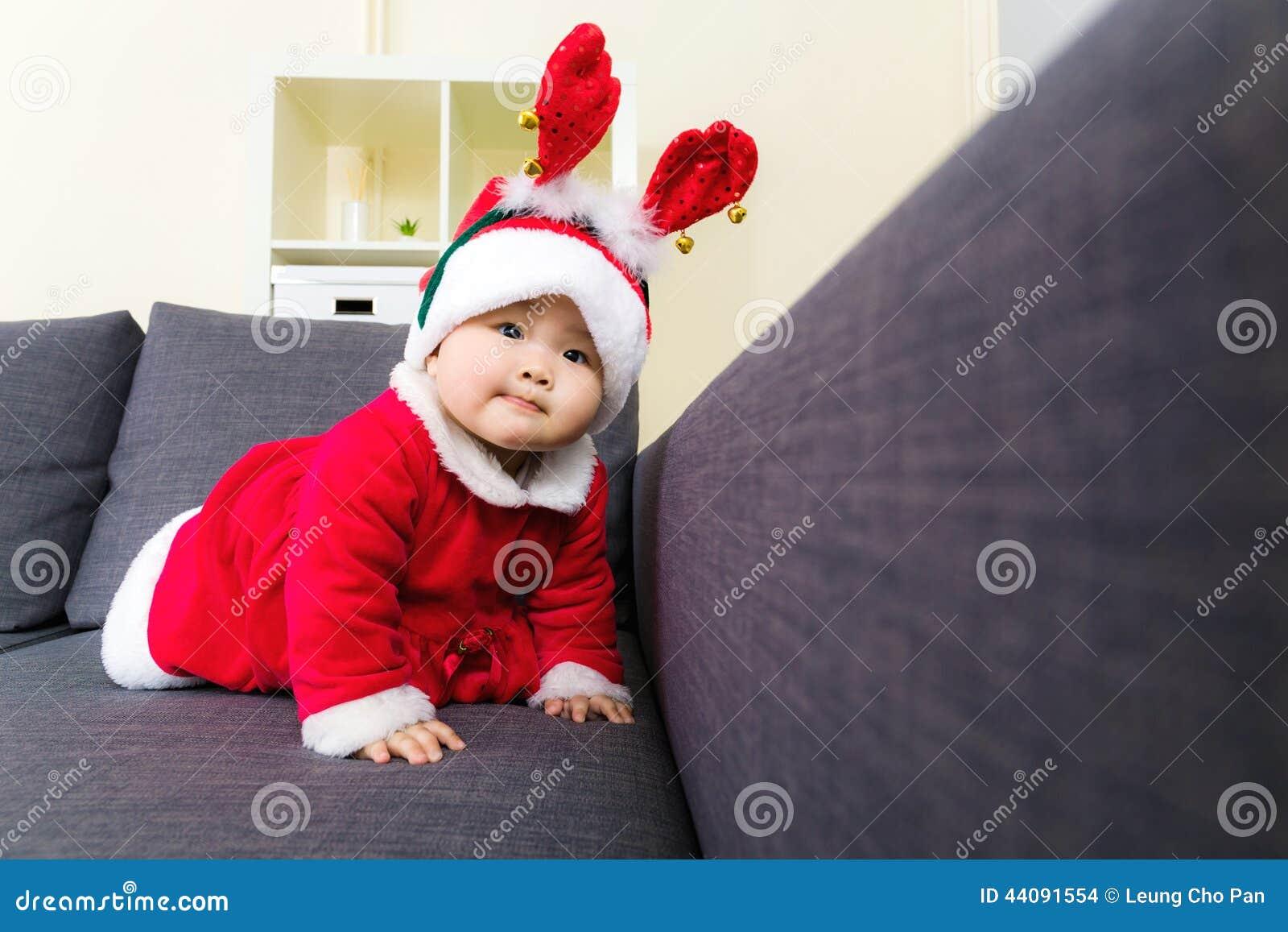 Bébé avec Noël s habillant et rampant sur le sofa