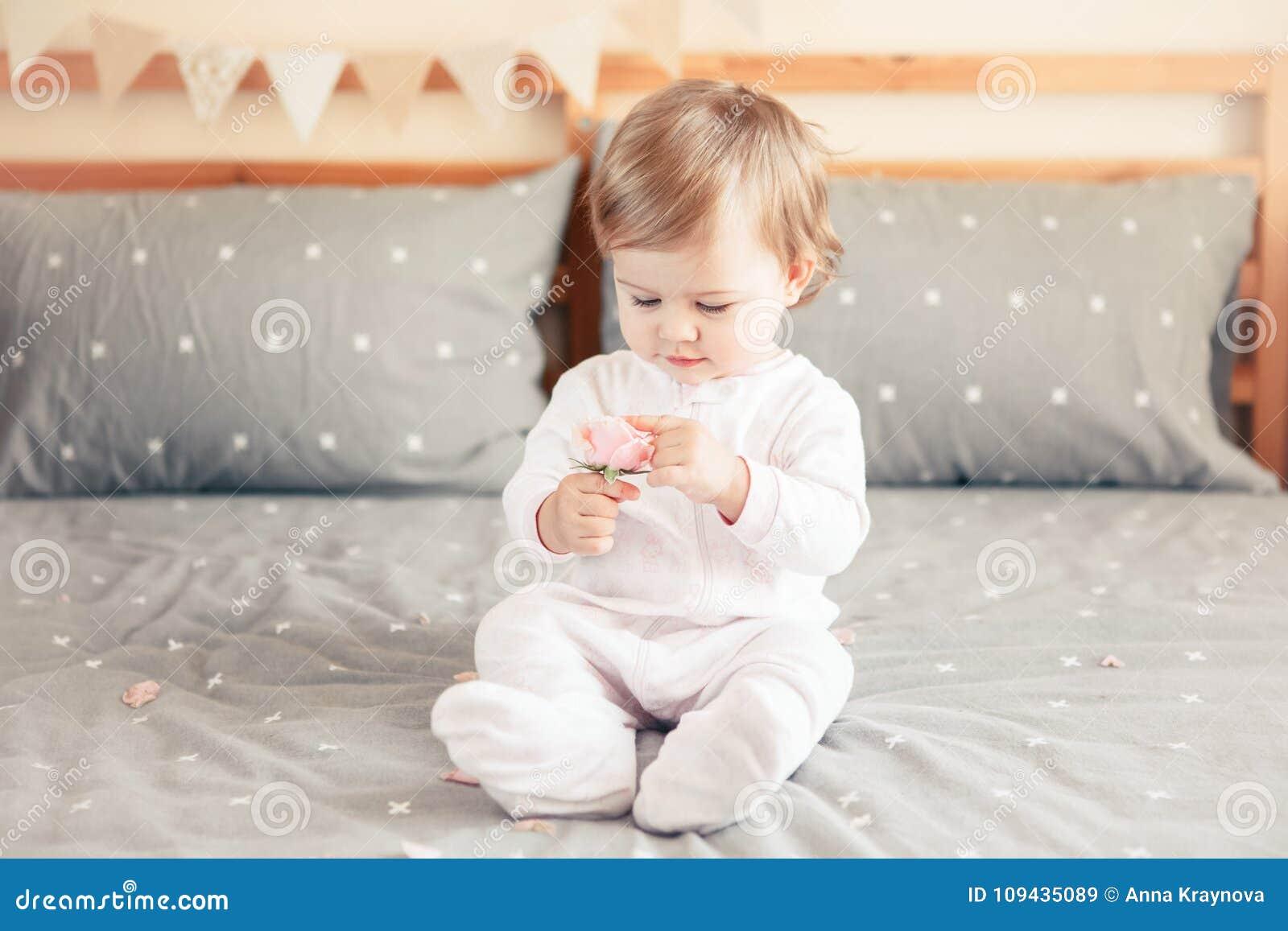 Bébé blond caucasien dans l onesie blanc se reposant sur le lit dans la chambre à coucher