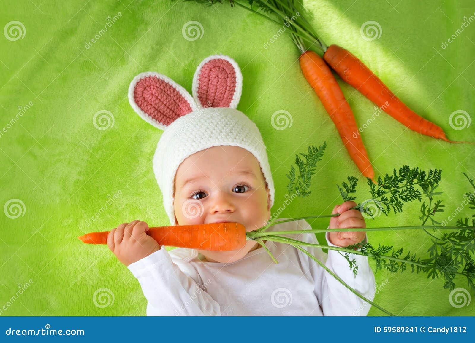Carotte Bleue se rapportant à bébé dans le chapeau de lapin mangeant la carotte image stock