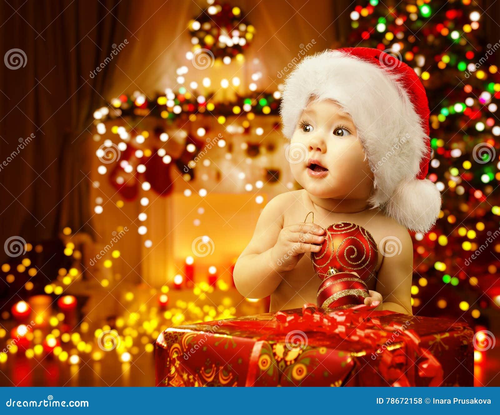 Bébé de Noël ouvrant l enfant actuel et heureux Santa Hat, cadeau de Noël