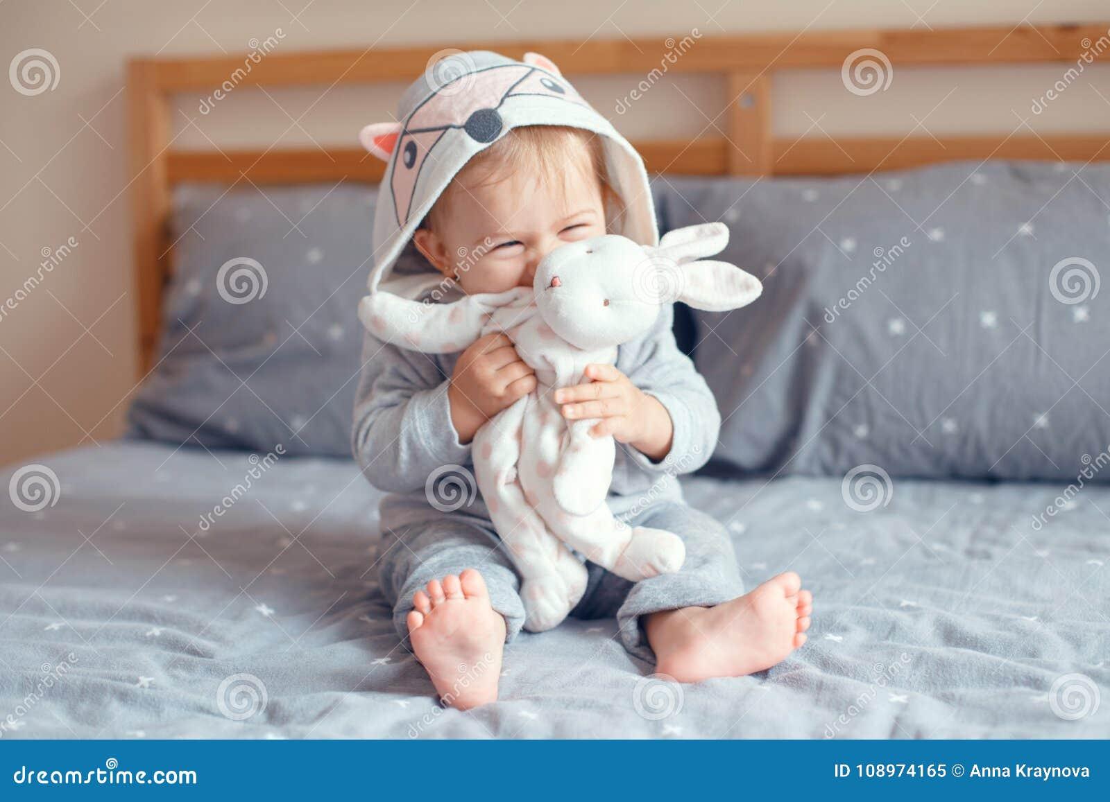 Bébé de sourire blond caucasien adorable mignon avec des yeux bleus