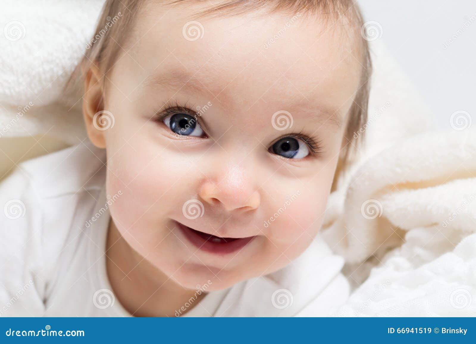Bébé de sourire sous une couverture