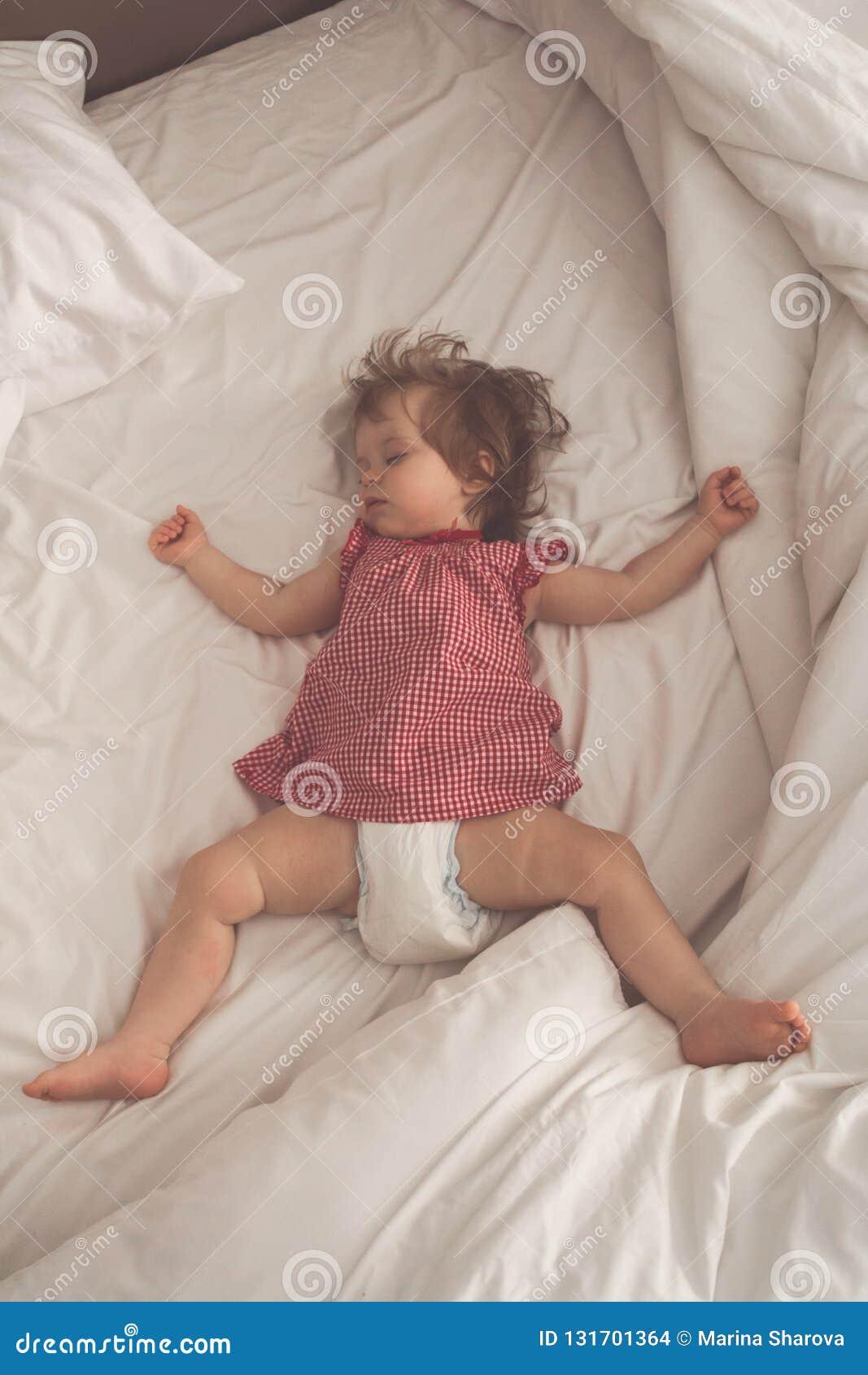 Bébé dormant sur le dos avec les bras ouverts et sans tétine dans un lit avec les feuilles blanches Sommeil paisible dans un lumi