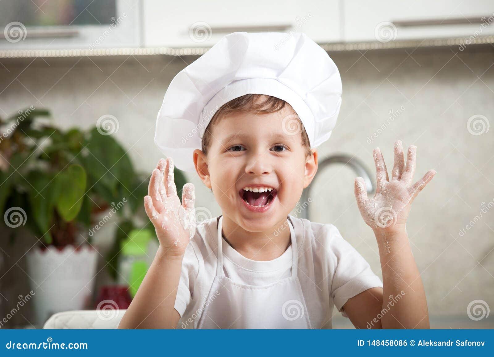B?b? dr?le avec de la farine, sourires ?motifs heureux de gar?on heureusement