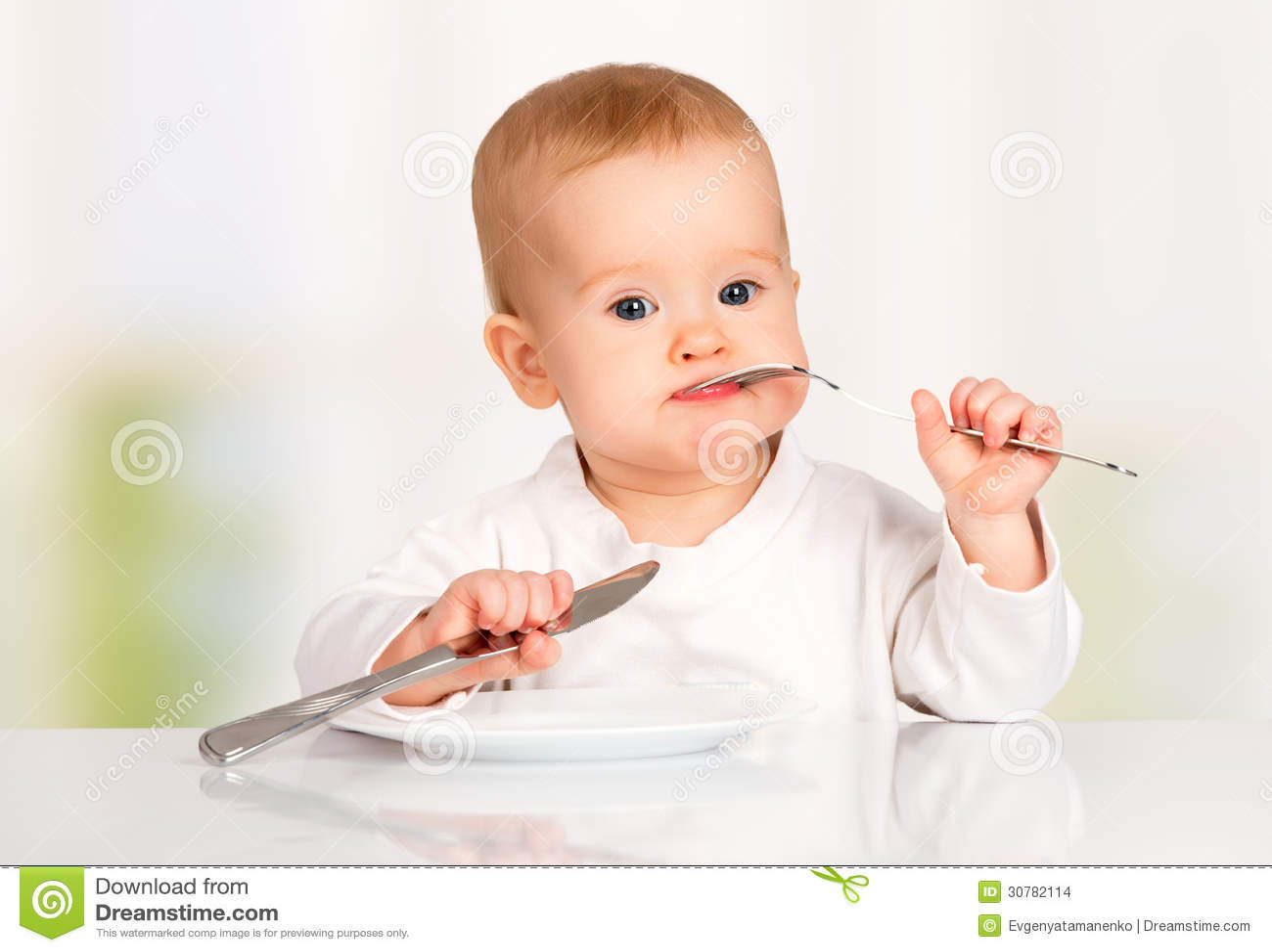 Bébé drôle avec un couteau et une fourchette mangeant de la nourriture