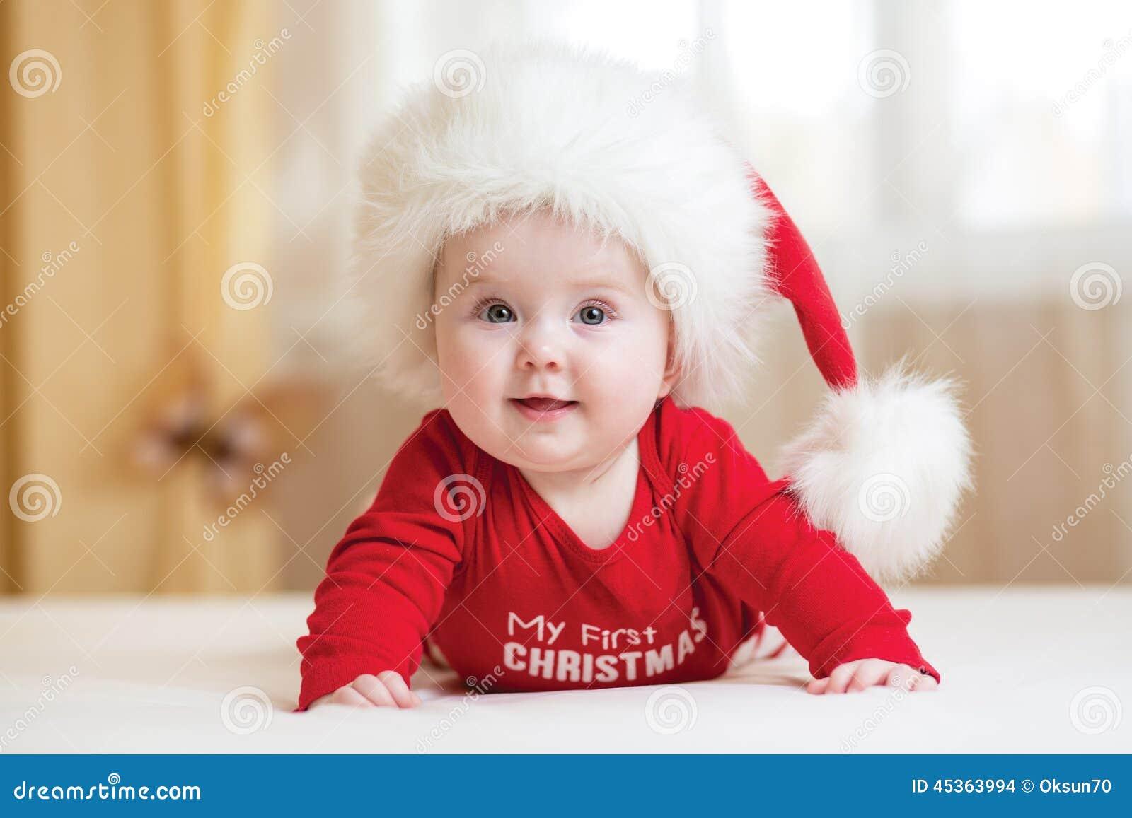 Bébé drôle de Santa se trouvant sur le lit