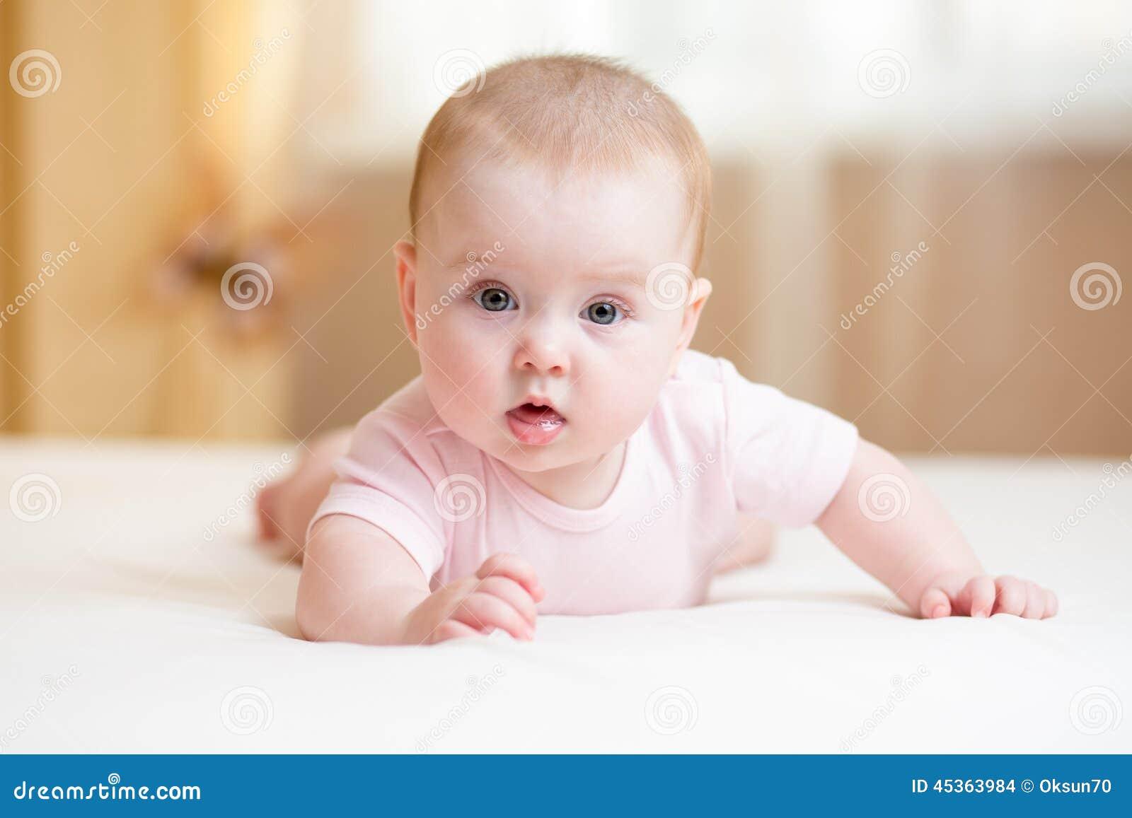 Bébé drôle se trouvant sur le lit