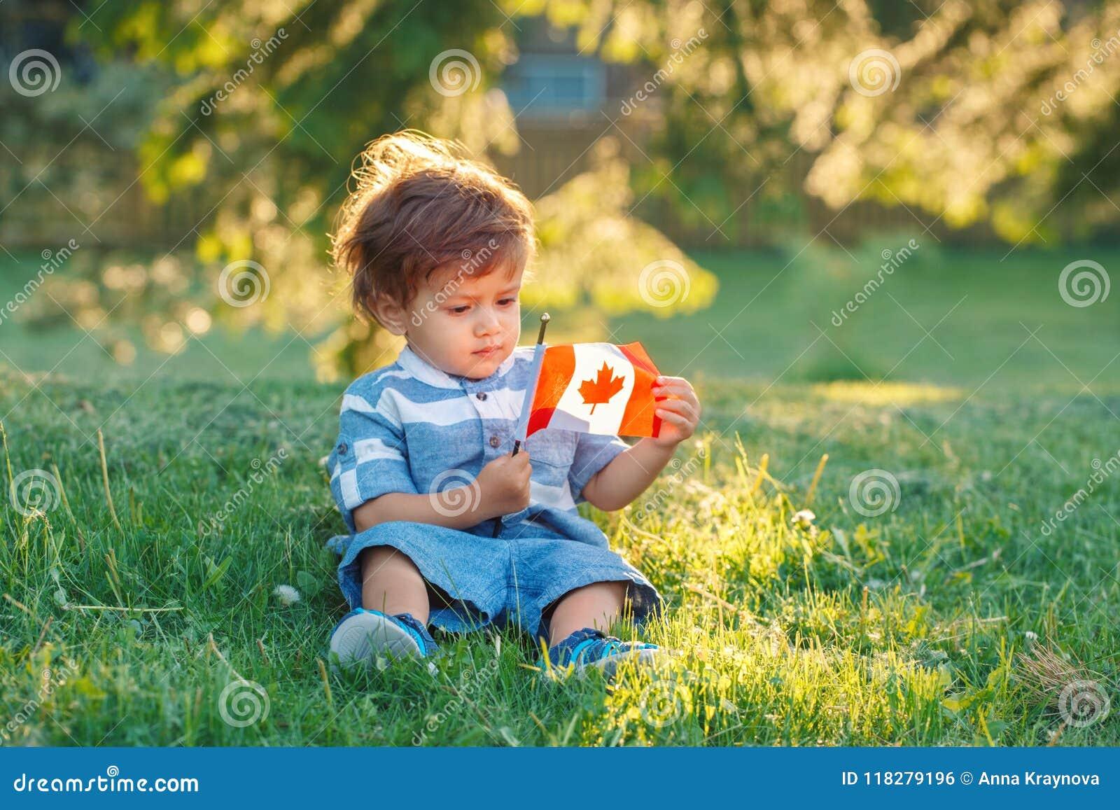 Bébé garçon caucasien tenant le drapeau canadien avec la feuille d érable rouge