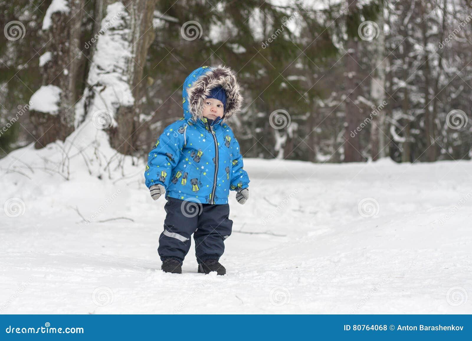 Bébé garçon dans la forêt de neige d hiver errant parmi des pins Garçon W