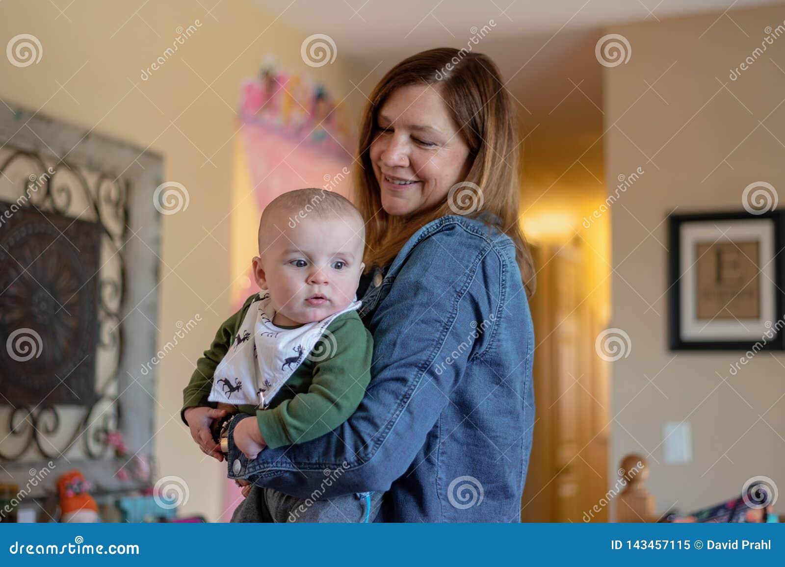 Bébé garçon de participation de femme tout en visitant avec la famille