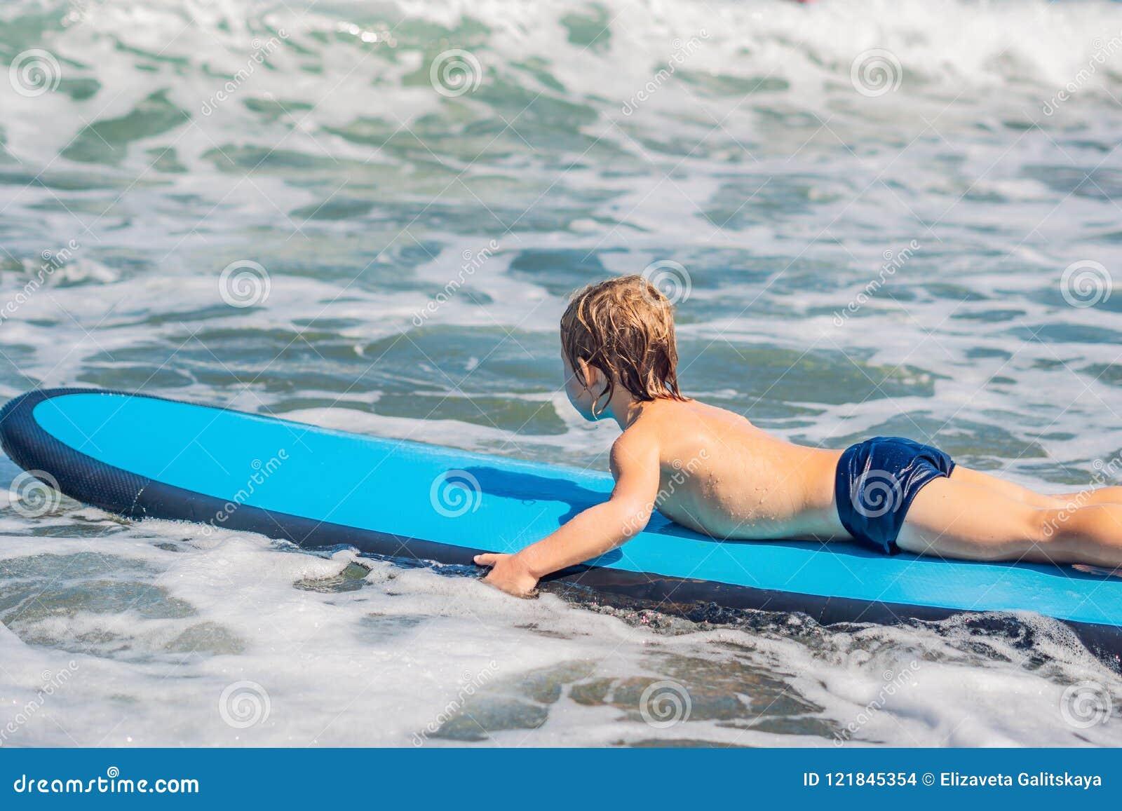 Bébé garçon heureux - jeune tour de surfer sur la planche de surf avec l amusement sur la mer