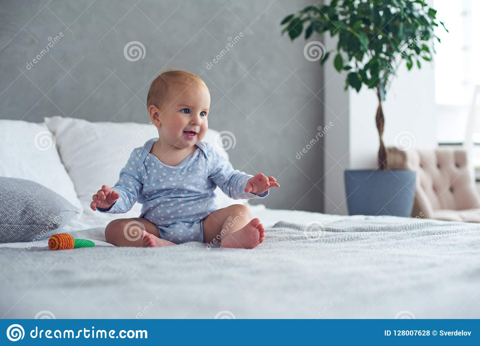 Bébé garçon mignon jouant avec le jouet tricoté sur le lit à la maison