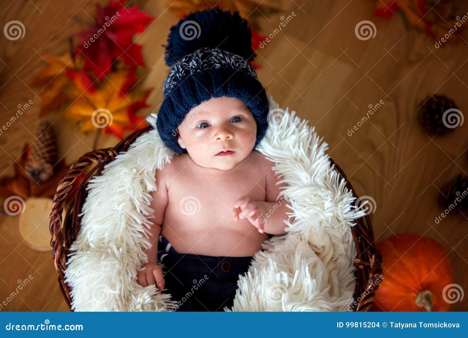 Bébé garçon nouveau-né mignon avec le chapeau tricoté dans un panier