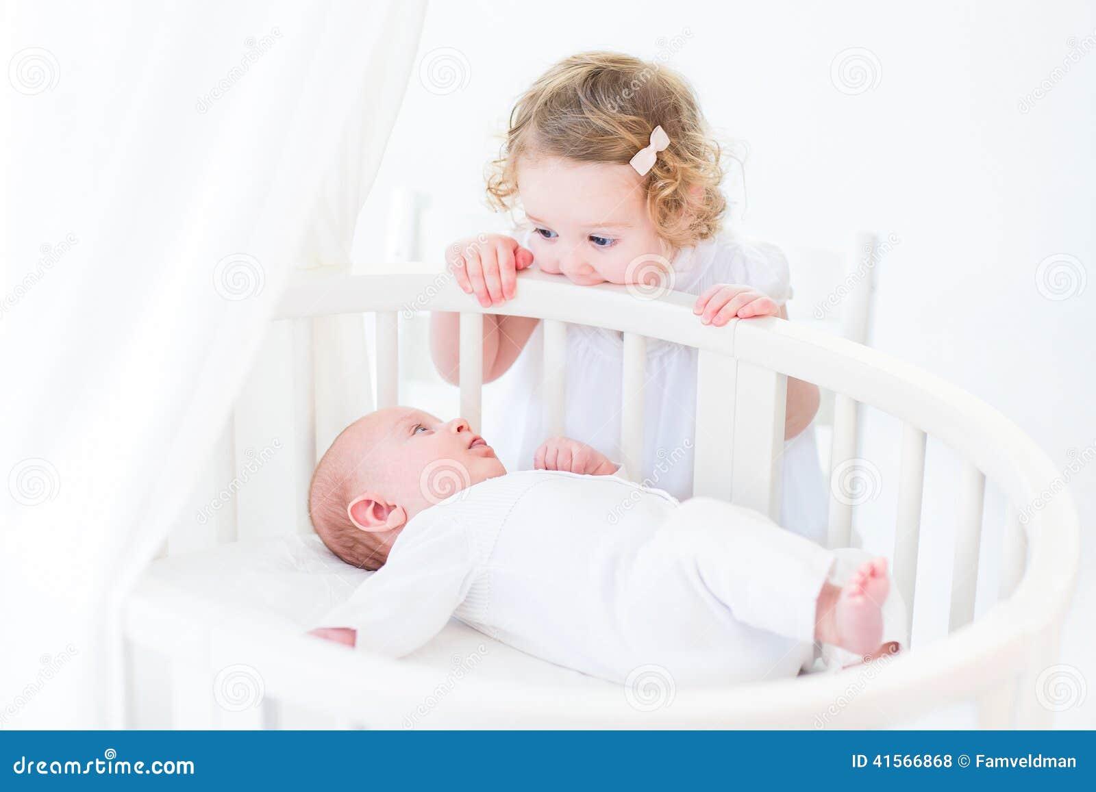 Bébé garçon nouveau-né mignon observant sa soeur d enfant en bas âge se tenir à salut