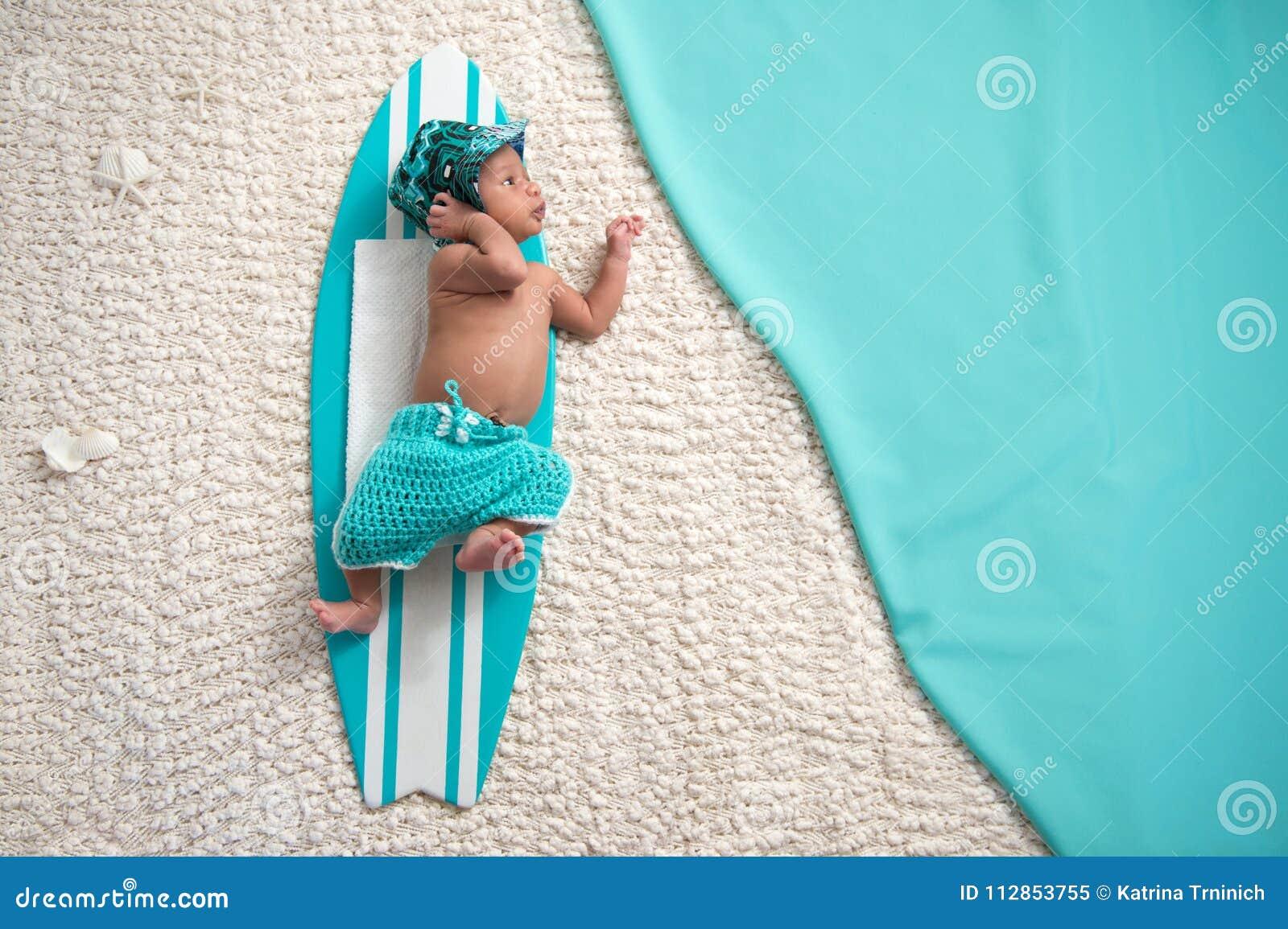 Bébé garçon nouveau-né sur la planche de surf