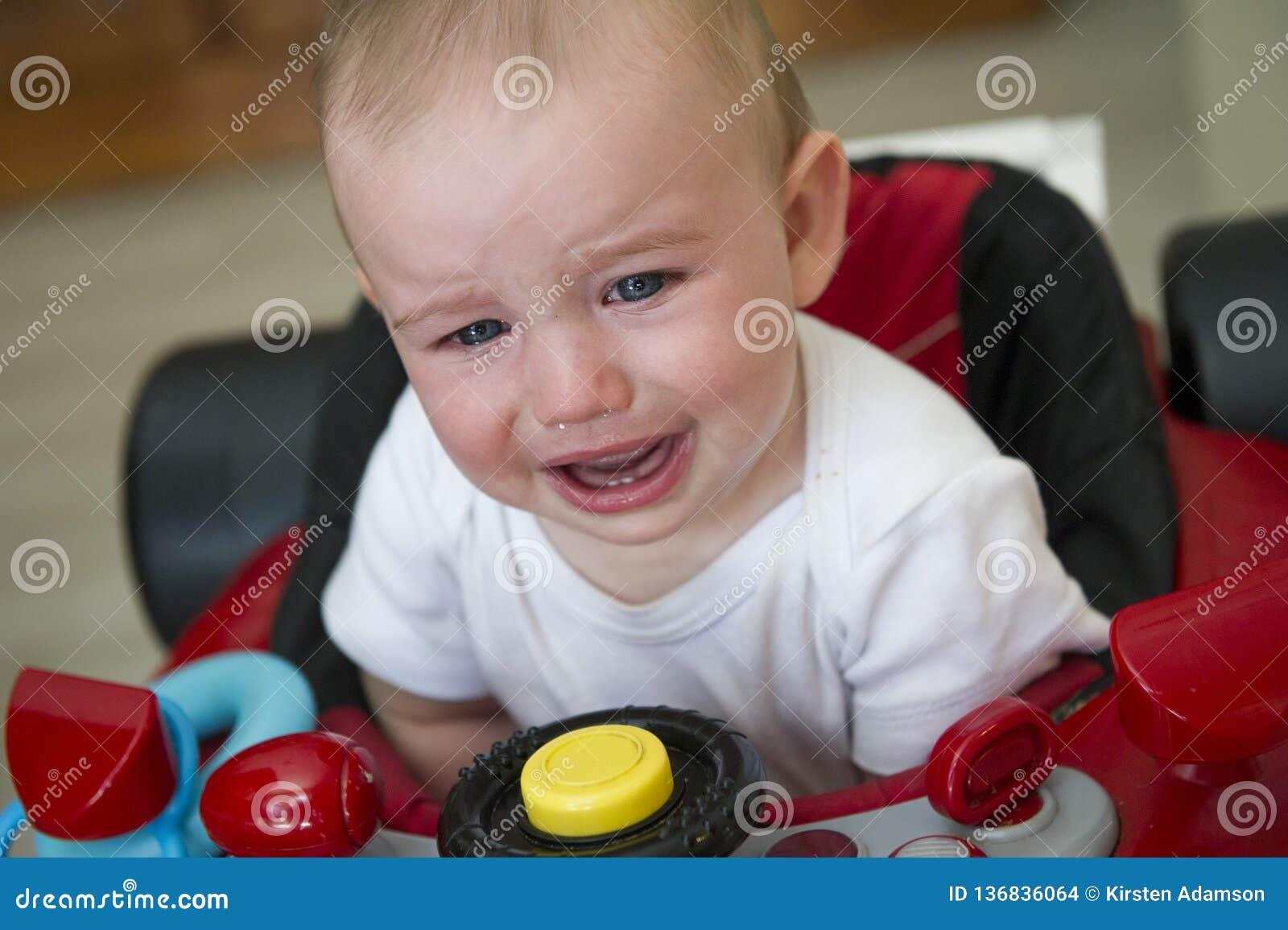 Bébé garçon pleurant dans un marcheur rouge de voiture de course