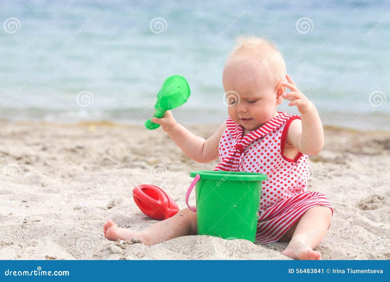 Bébé jouant sur la plage sablonneuse