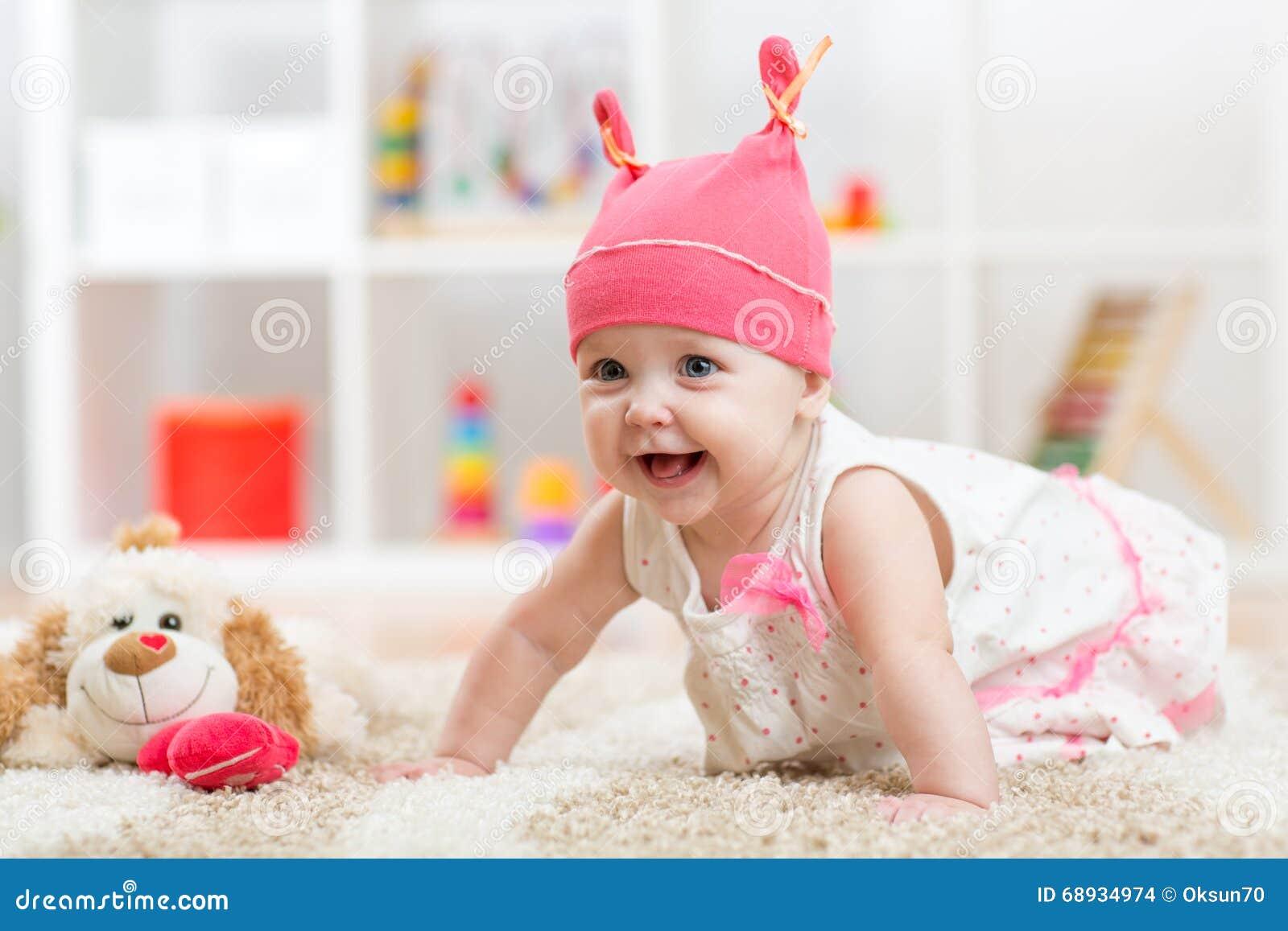 Bébé mignon avec le jouet rampant sur le plancher