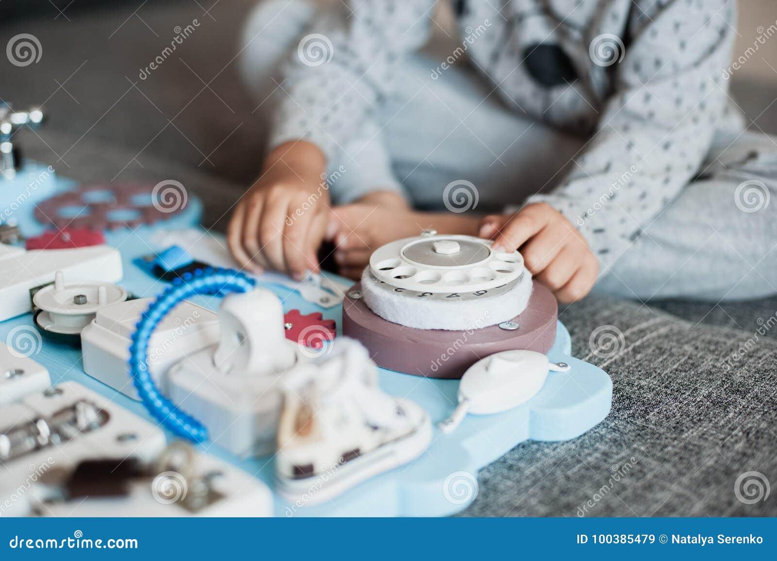 Bébé mignon d enfant en bas âge jouant avec le conseil occupé à la maison