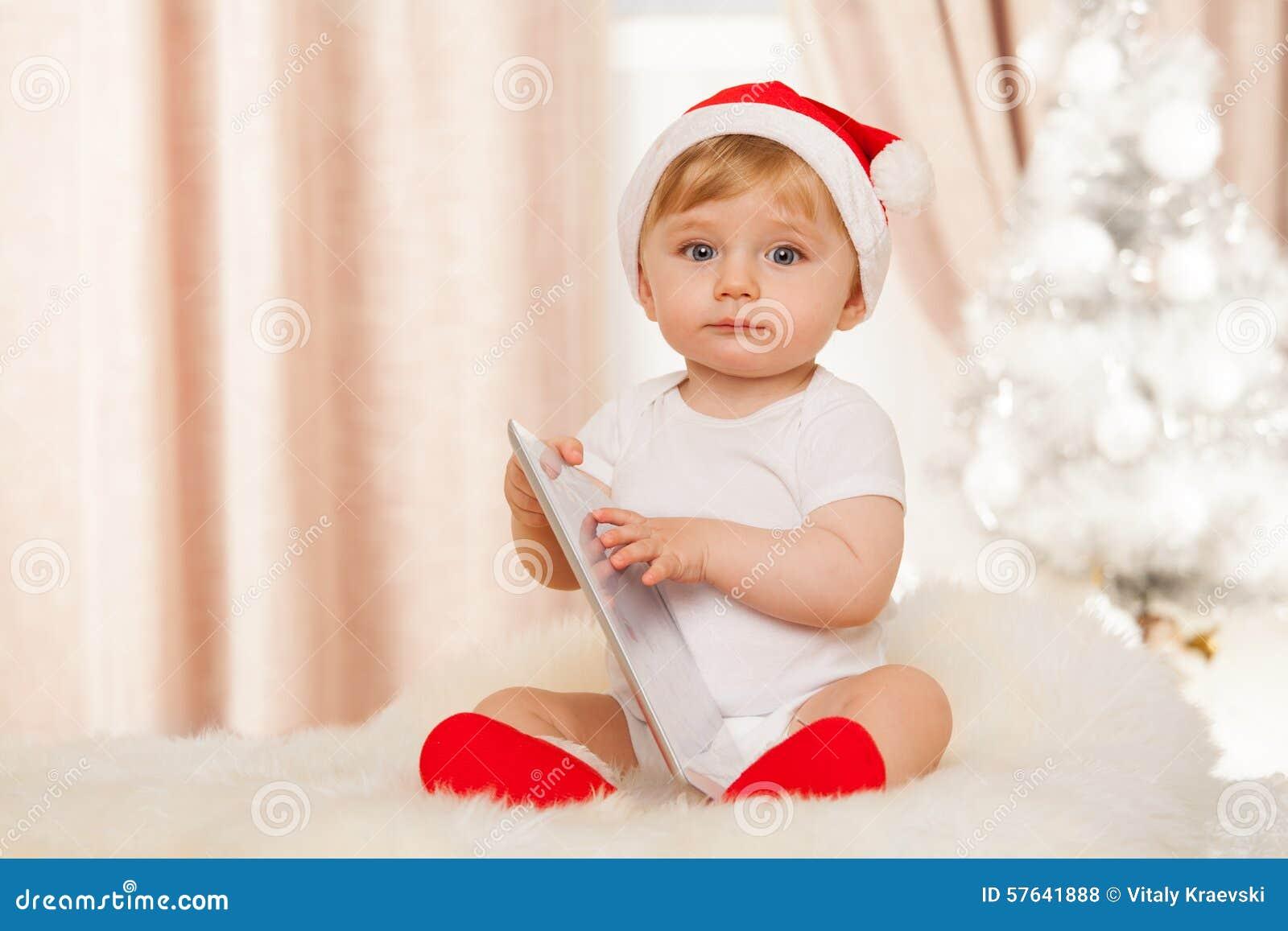 Bébé mignon de Santa avec le comprimé