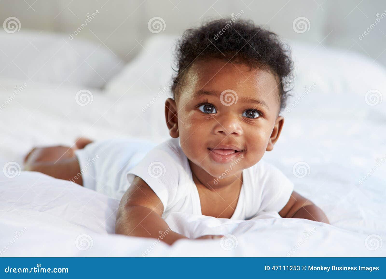 Bébé mignon se trouvant sur le ventre dans le lit du parent