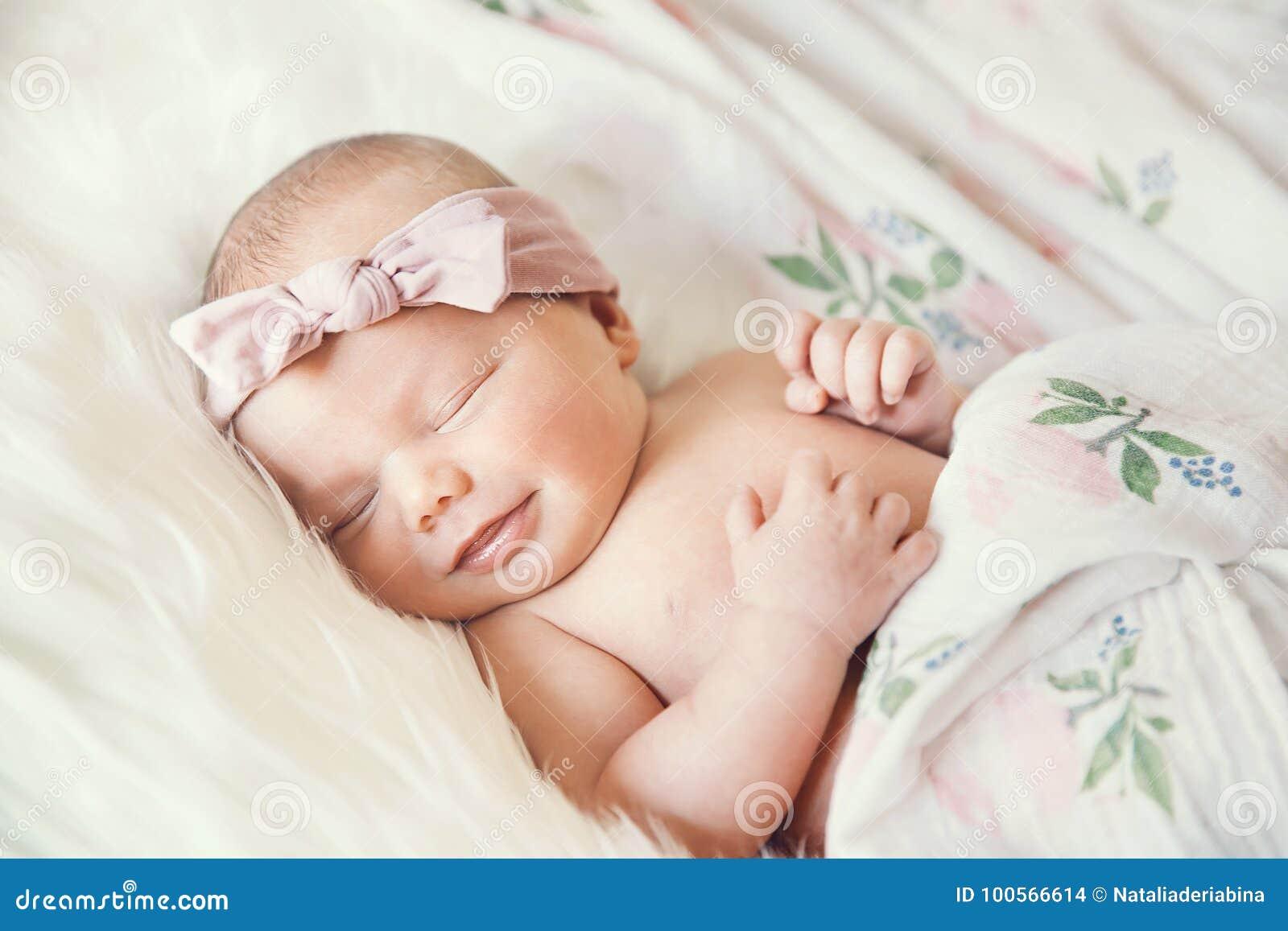 Bébé nouveau-né de sourire de sommeil dans une enveloppe sur la couverture blanche