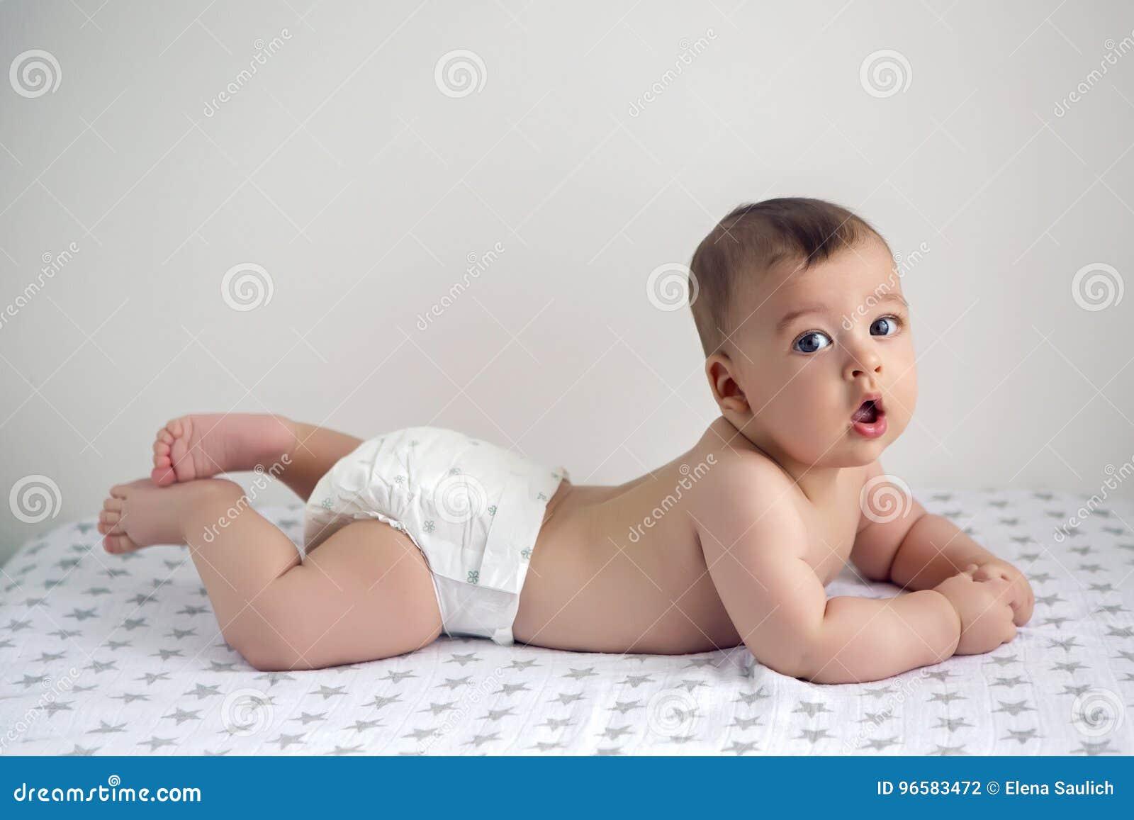 e8386e007f1e8 Bébé nu dans des couches-culottes se trouvant sur son ventre sur la couche-culotte  avec des étoiles
