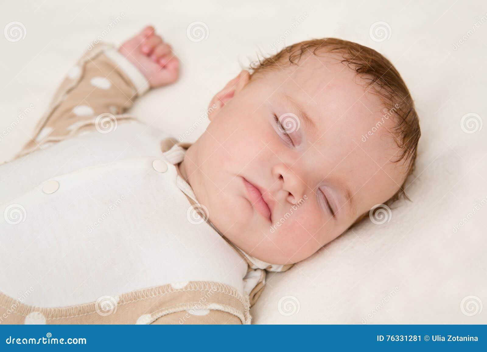 Bébé paisible se trouvant sur un lit tout en dormant