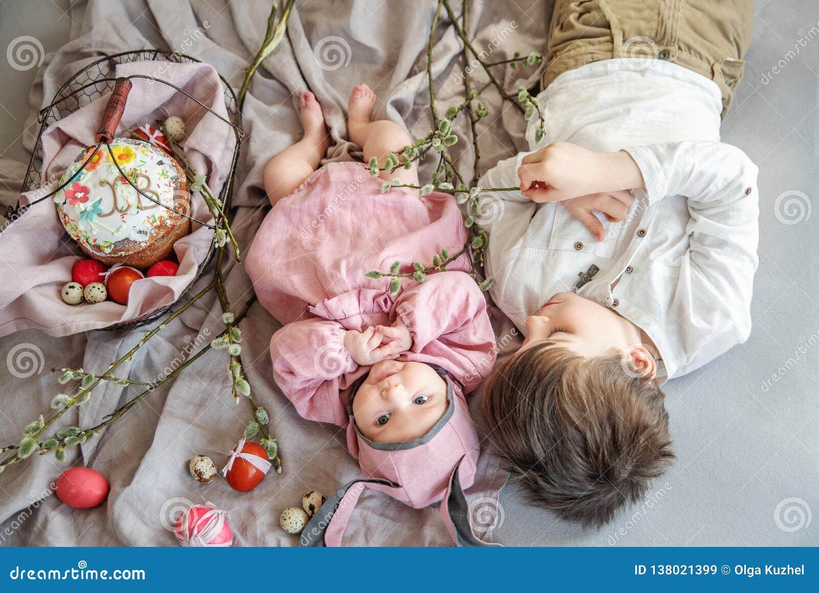 Bébé se trouvant sur la couverture de toile et utilisant un chapeau sous forme de lapin de Pâques avec son frère près des branche