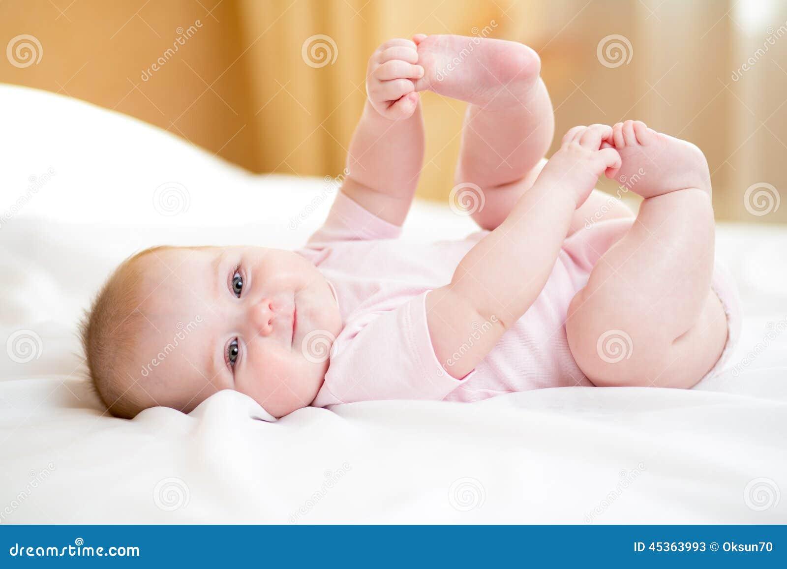 Bébé se trouvant sur la feuille blanche et tenant des jambes