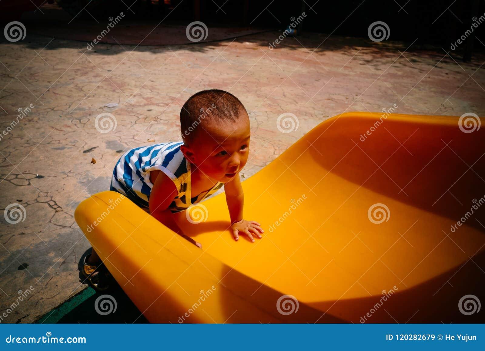 Bébé sur la glissière de terrain de jeu