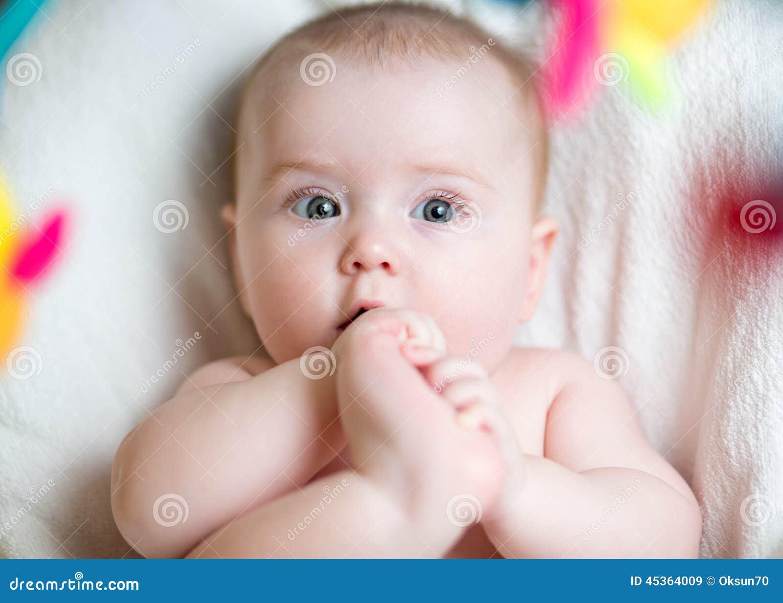 Bébé tirant le pied à la bouche