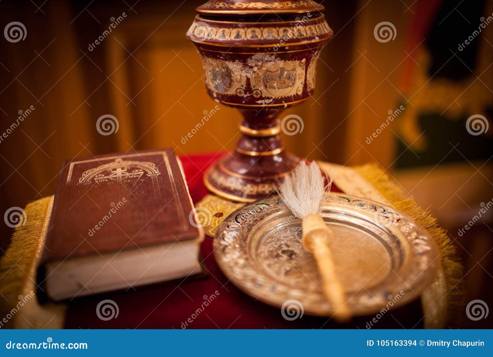 A Bíblia ortodoxo, cruz e uma mecha em um pano para o batismo