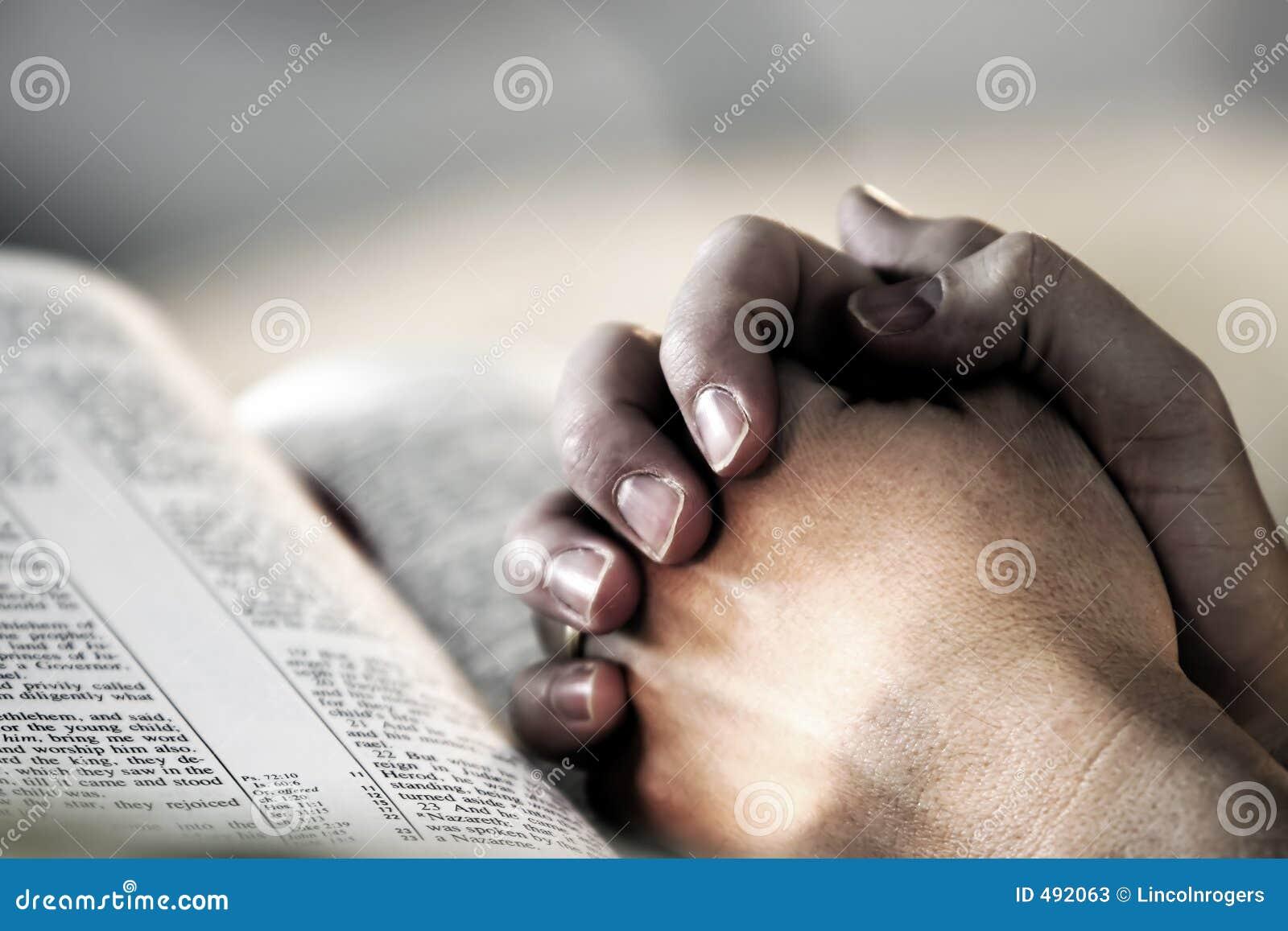 A Bíblia Praying das mãos