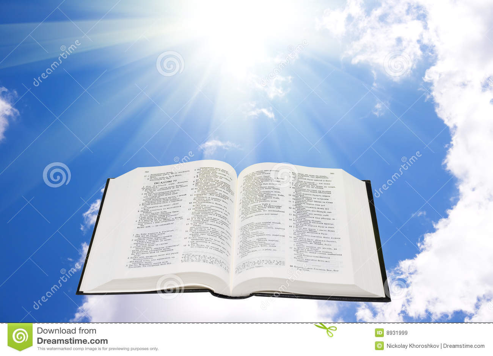 A Bíblia santamente no céu iluminado por uma luz solar
