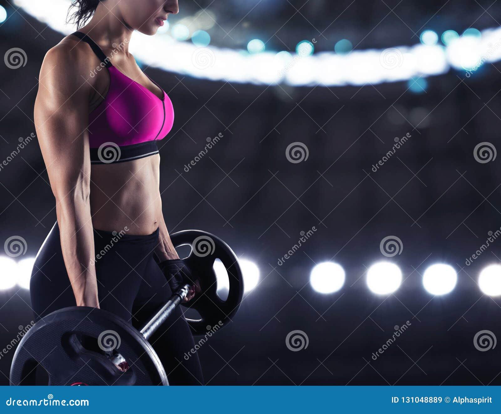 Bíceps atlético do treinamento da mulher no gym