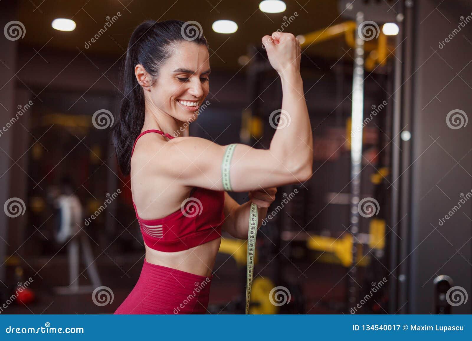 Bíceps de medición sonriente de la mujer