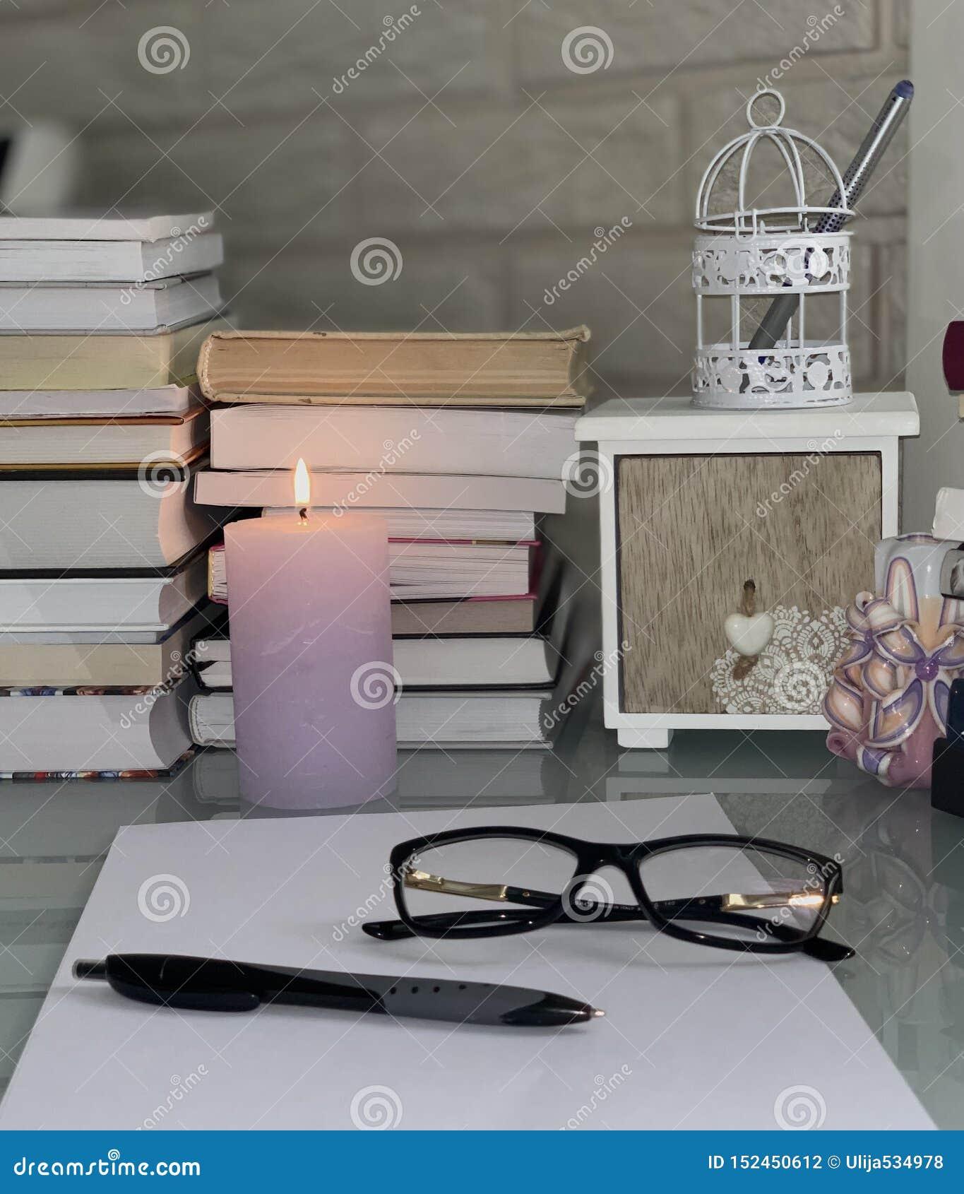 Böcker på tabellen, en lila brinnande stearinljus, exponeringsglas, papper, penna, ask