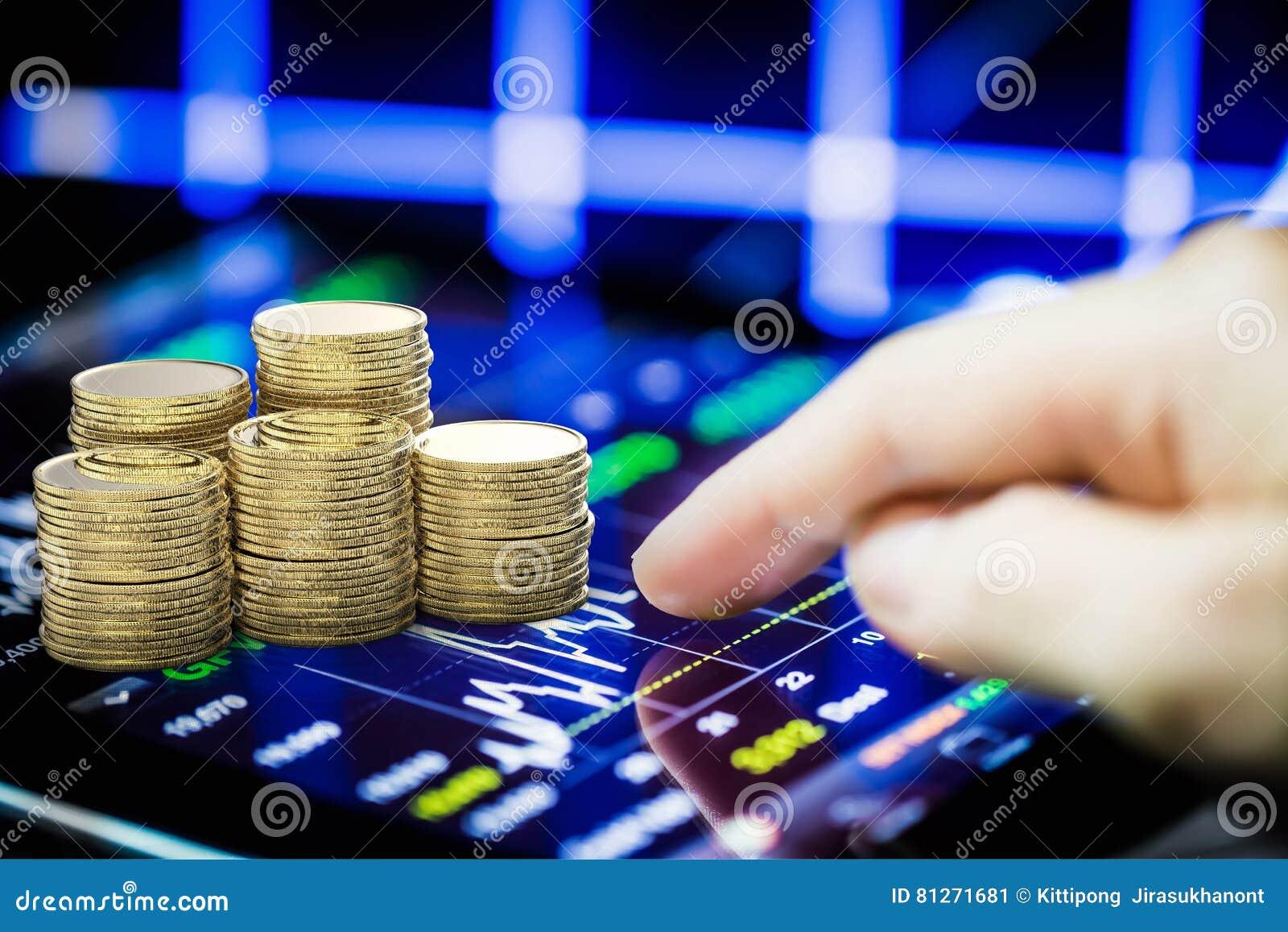 Börse, die mit digitaler Tablette und Stapel der Goldmünze aufpasst