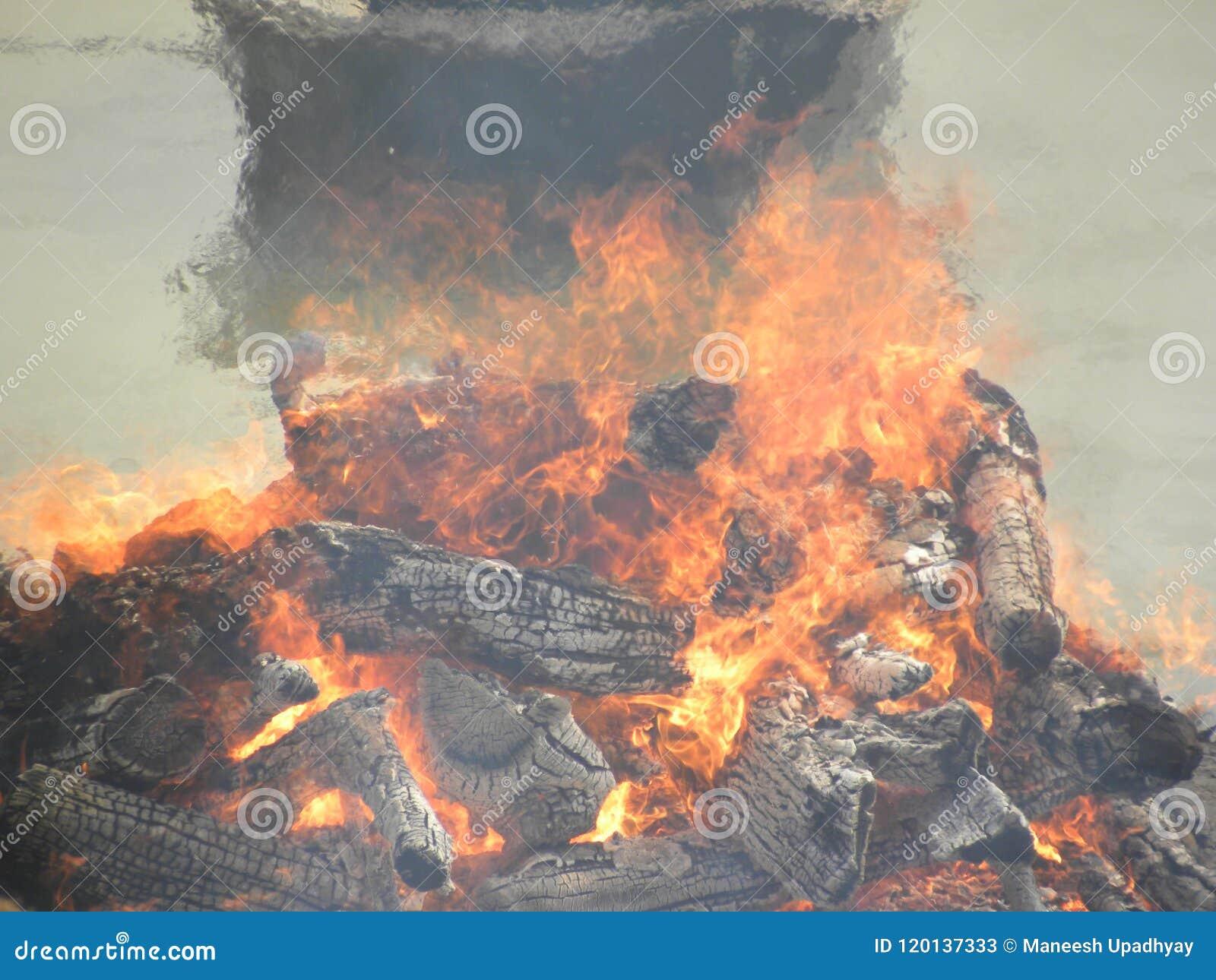 Bûcher funèbre avec du bois et des flammes du feu aux au sol d incinération