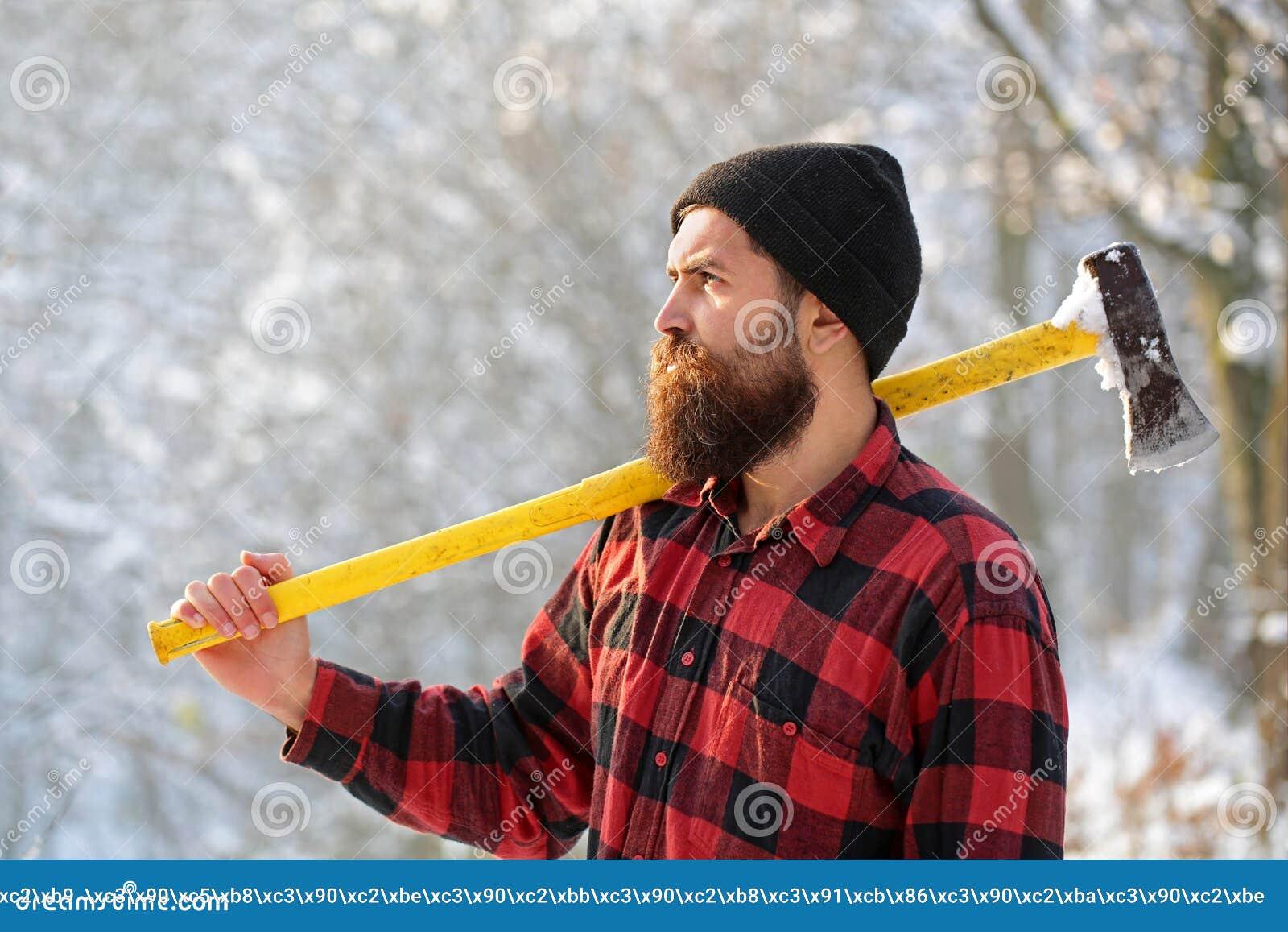 Bûcheron dans les bois avec une hache Homme barbu dans le chapeau avec une cognée Homme bel, hippie Barbu brutal de bûcheron