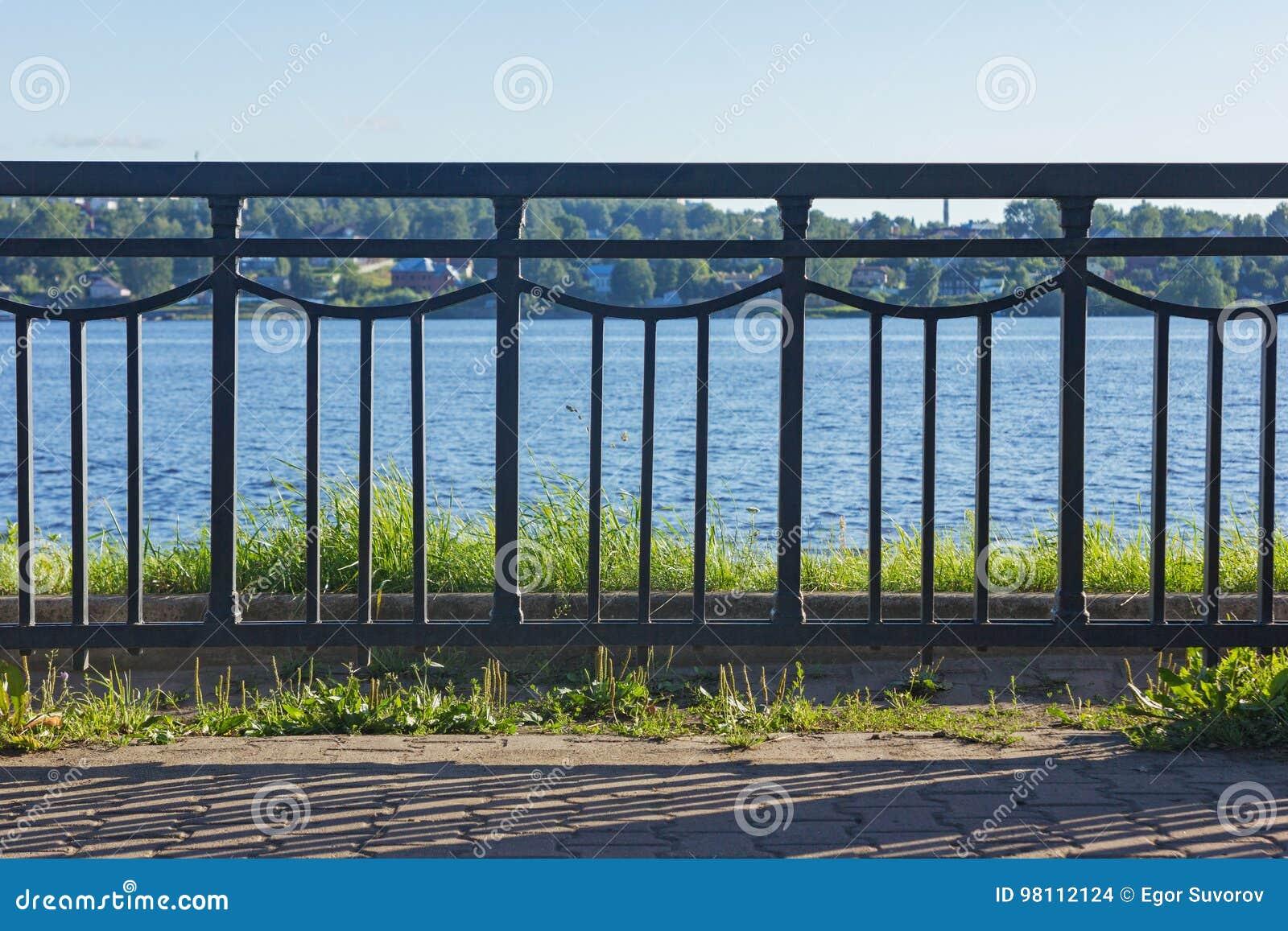 Bügeln Sie Zaun vor dem Fluss an einem sonnigen Tag