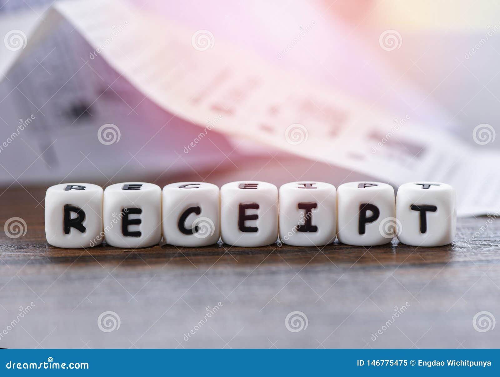 Büro des Empfangspapiers auf dem Tisch mit würfelt WortBareinnahmen-Einkaufslistepapier-Registrierkasse-Lohnliste