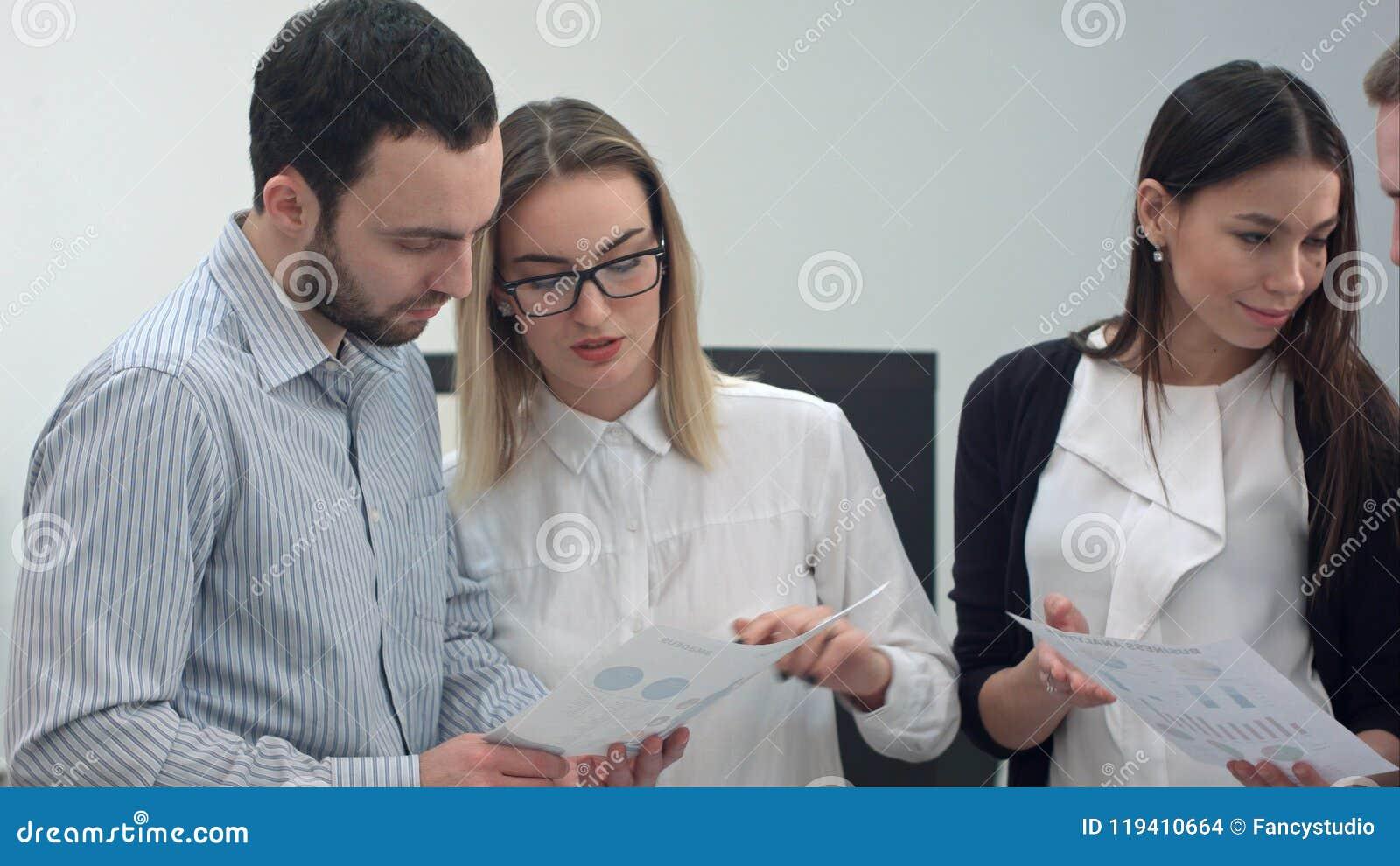 Büroangestellte, die Darstellungsmaterialien besprechen