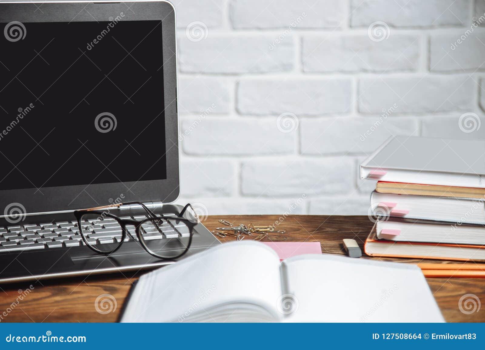 Büroarbeitsplatz mit offenem Laptop Arbeitsplatz des Geschäftsmannes oder des Studenten - Notizbücher, Stift, Bücher, Kopfhörer a