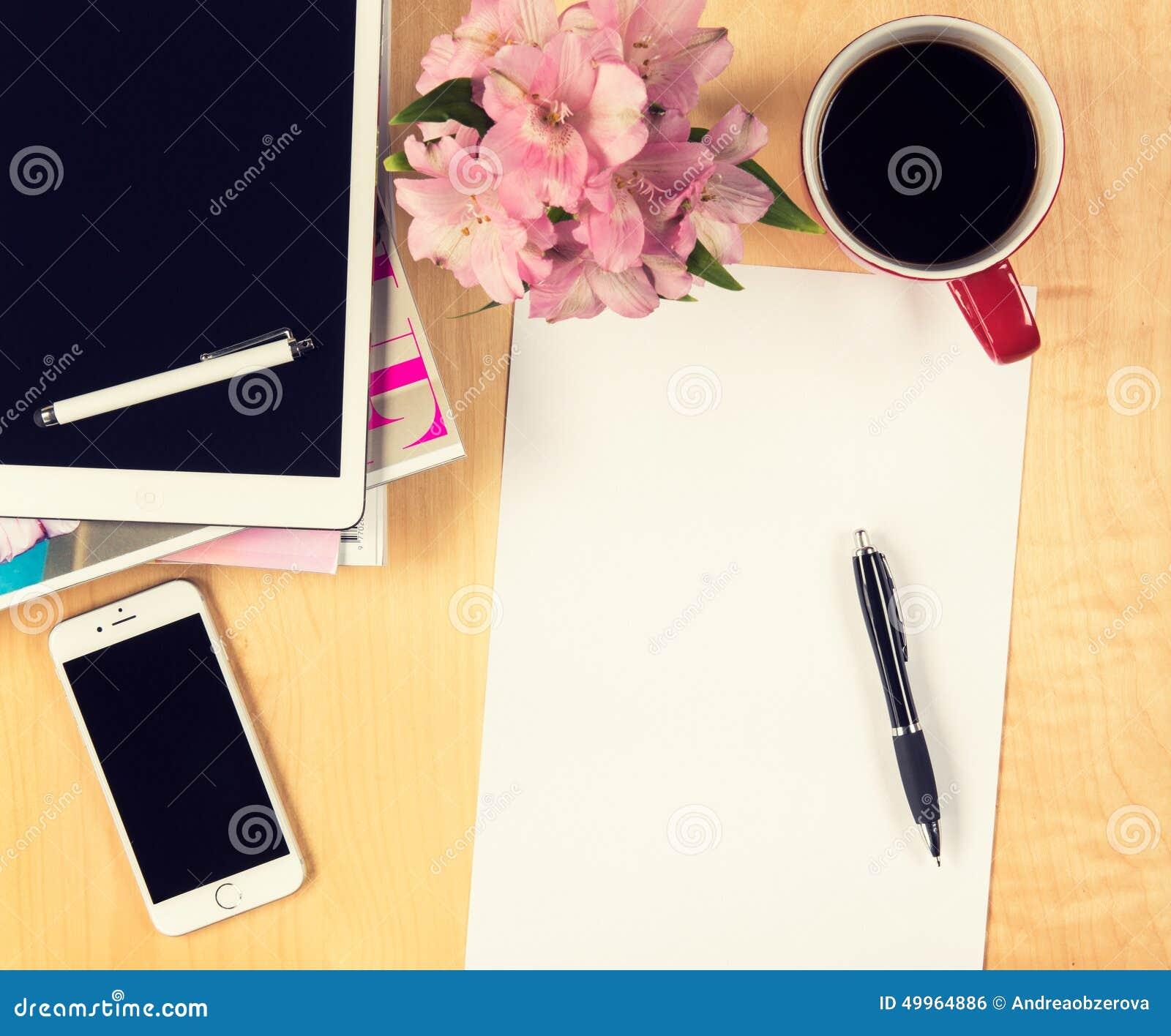 Bürotisch mit digitaler Tablette, leerem Blatt Papier des Smartphone und Tasse Kaffee Ansicht von oben