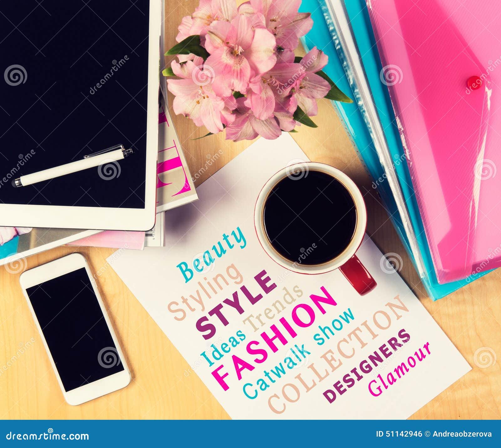 Bürotisch mit Modezeitschriften, digitaler Tablette, Smartphone und Tasse Kaffee Ansicht von oben