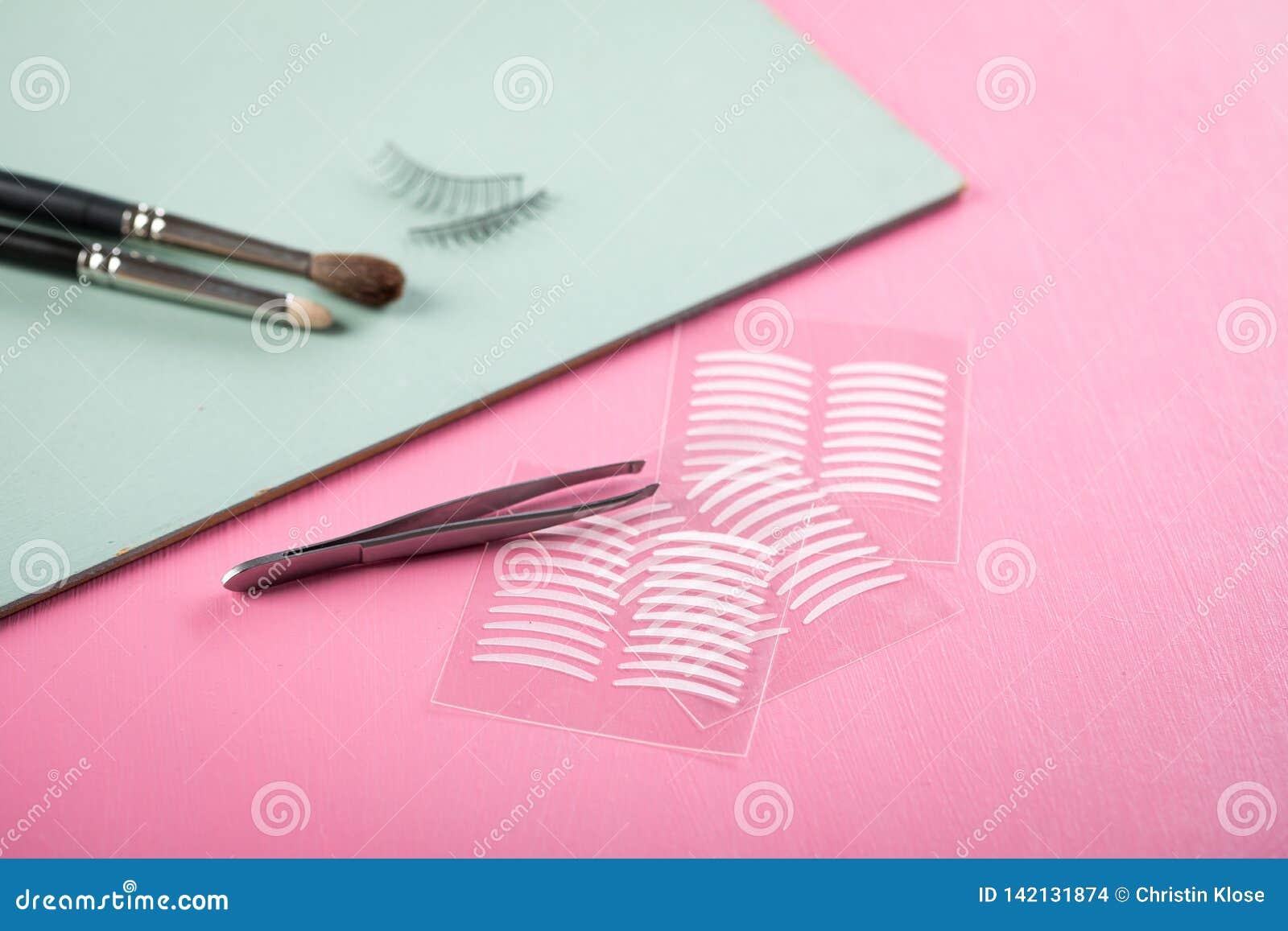 Bürsten, gefälschte Peitschen, Pinzette und doppelte Bänder der künstlichen Augenlidfalte für Augenmake-up auf rosafarbenem Paste